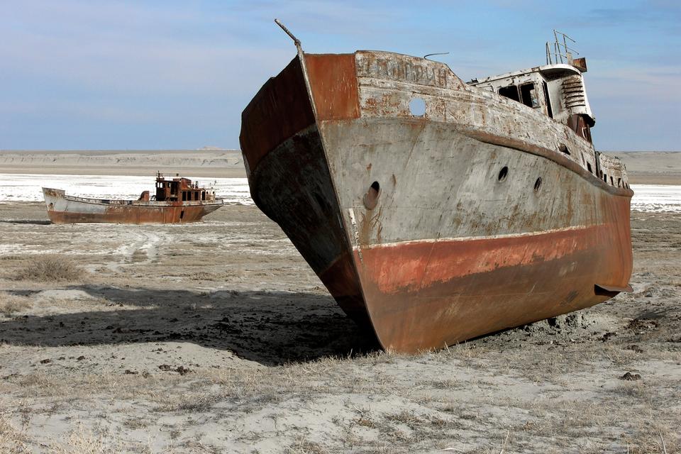 Fotografia prezentuje zardzewiały wrak statku stojący na suchym lądzie.
