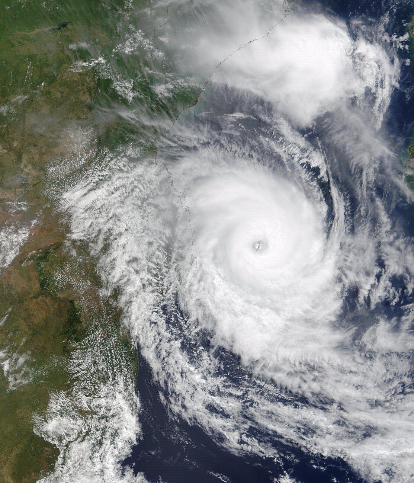 Zdjęcie satelitarne przedstawia wirujący cyklon widziany zgóry. Wcentralnej części zdjęcia znajduje się skupisko wirujących białych chmur. Wewnątrz kręgu, które tworzą wirujące chmury, tworzy się lej. Pusta przestrzeń wewnątrz cyklonu to bezchmurny obszar nazywany okiem cyklonu.