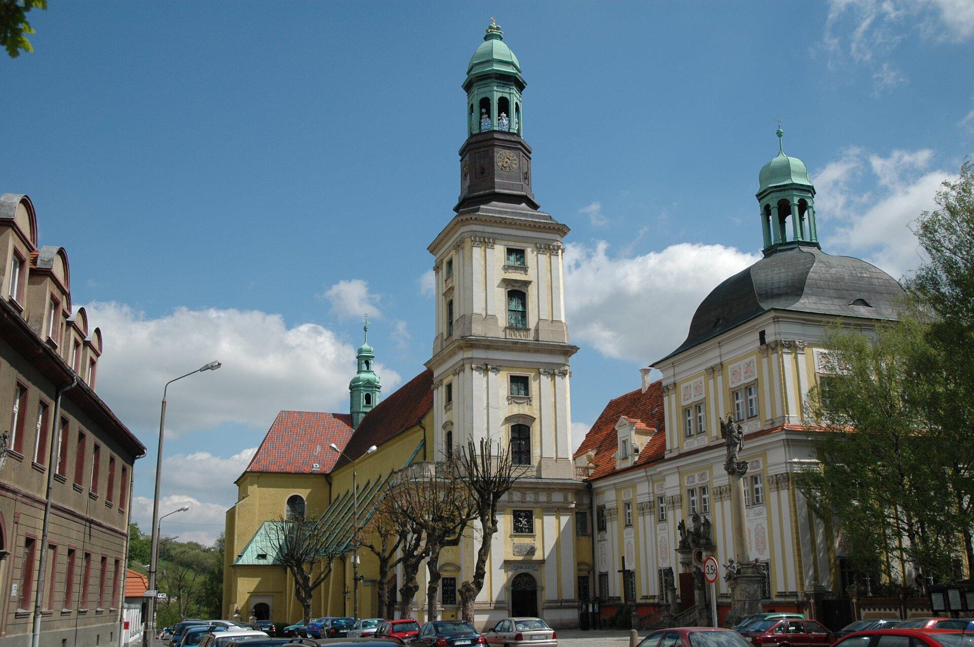 Na zdjęciu Sanktuarium św. Jadwigi iśw. Bartłomieja wTrzebnicy. Zespół klasztorny wraz zbazyliką. Przed bazyliką Kolumna św. Jana Nepomucena. Fasada budynków wkolorze żółtym ibiałym. Dachy czerwone, wieże zielone.