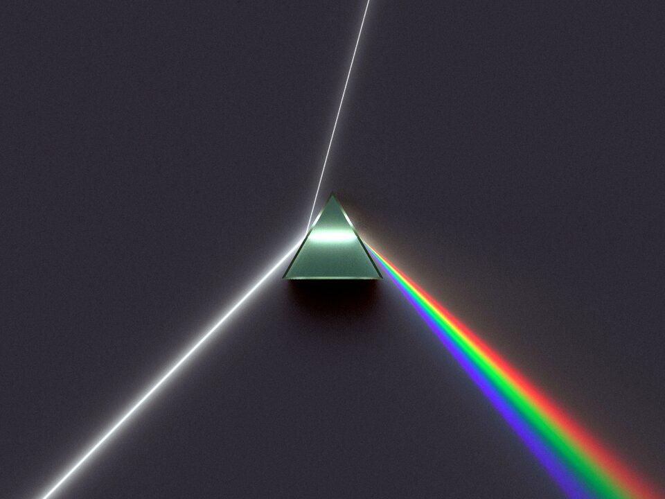 Zdjęcie przedstawia trójkątny pryzmat ze szkła kwarcowego leżący na ciemnym podłożu. Zlewej strony pod niewielkim kątem na powierzchnię boczną pryzmatu pada wąska wiązka białego światła iczęściowo odbija się wgórę. Większa część wiązki wnika jednak wpryzmat iprzechodzi przez niego na drugą stronę, gdzie na przeciwległej krawędzi rozprasza się wtęczowy słup. Słup ten, wmiarę oddalania się od pryzmatu staje się coraz szerszy.