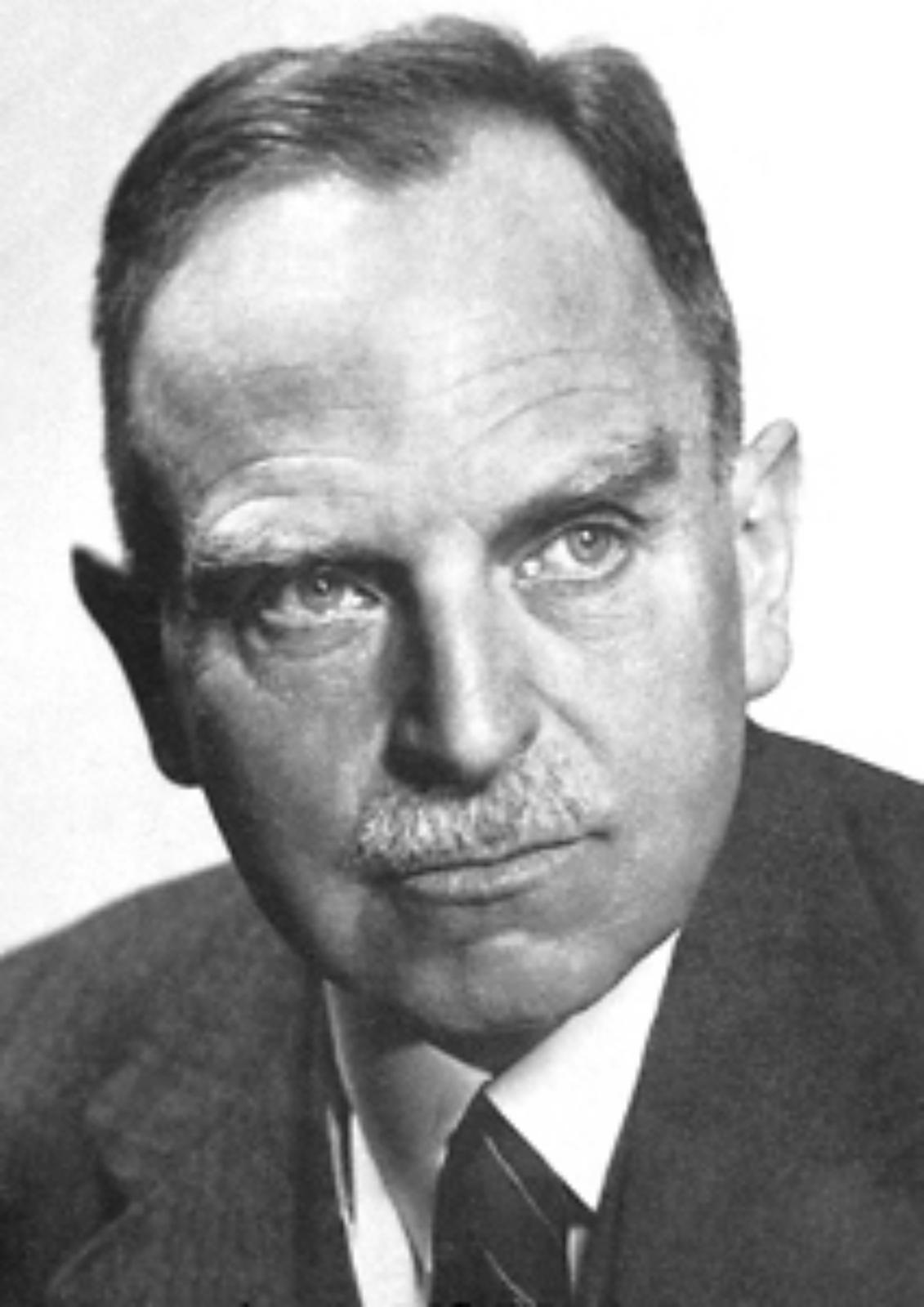 Zdjęcie przedstawia Otto Hahna. Fotografia czarno-biała. Mężczyzna wwieku ok. 55 lat. Włosy ciemne, przerzedzone. Czoło wysokie, widoczne zmarszczki poprzeczne. Oczy jasne. Nos prosty. Usta wąskie, dolna warga nieco większa. Krótko przystrzyżone, siwe wąsy. Uszy średniej wielkości, górna część małżowiny usznej delikatnie odstająca. Mężczyzna jest ubrany wmarynarkę, białą koszulę iciemny krawat wwąskie paski.