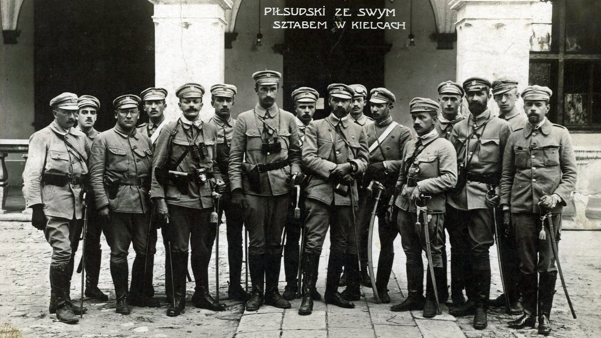 """Czarno-biała fotografia przedstawia grupę 16 żołnierzy ubranych wmundury polskich legionistów. Każdy znich ma przy pasie szablę. Wcentrum stoi Józef Piłsudski, po jego prawej ilewej stronie stoją członkowie sztabu. Ugóry zdjęcia widnieje napis: """"PIŁSUDSKI ZE SWYM SZTABEM WKIELCACH"""". Zdjęcie zrobiono przed pałacem. Grupa stoi ustawiona na tle pałacowego wejścia ozdobionego dwoma kolumnami. Pod zdjęciem zamieszczono informację ookolicznościach, wjakich zostało ono zrobione iprzedstawionych na nim postaciach: """" Sztab oficerów legionowych wKielcach, rok 1914. Od lewej: Ignacy Boerner, Zygmunt Sulistrowski, Aleksander Litwinowicz, Władysław Stryjeński, Michał Sokolnicki, NN, Kazimierz Sosnkowski, Michał Fuksiewicz, Józef Piłsudski, Michał Sawicki, Władysław Belina-Prażmowski, Mieczysław Trojanowski, Julian Stachiewicz, Walery Sławek, Roman Horoszkiewicz iGustaw Daniłowski."""""""