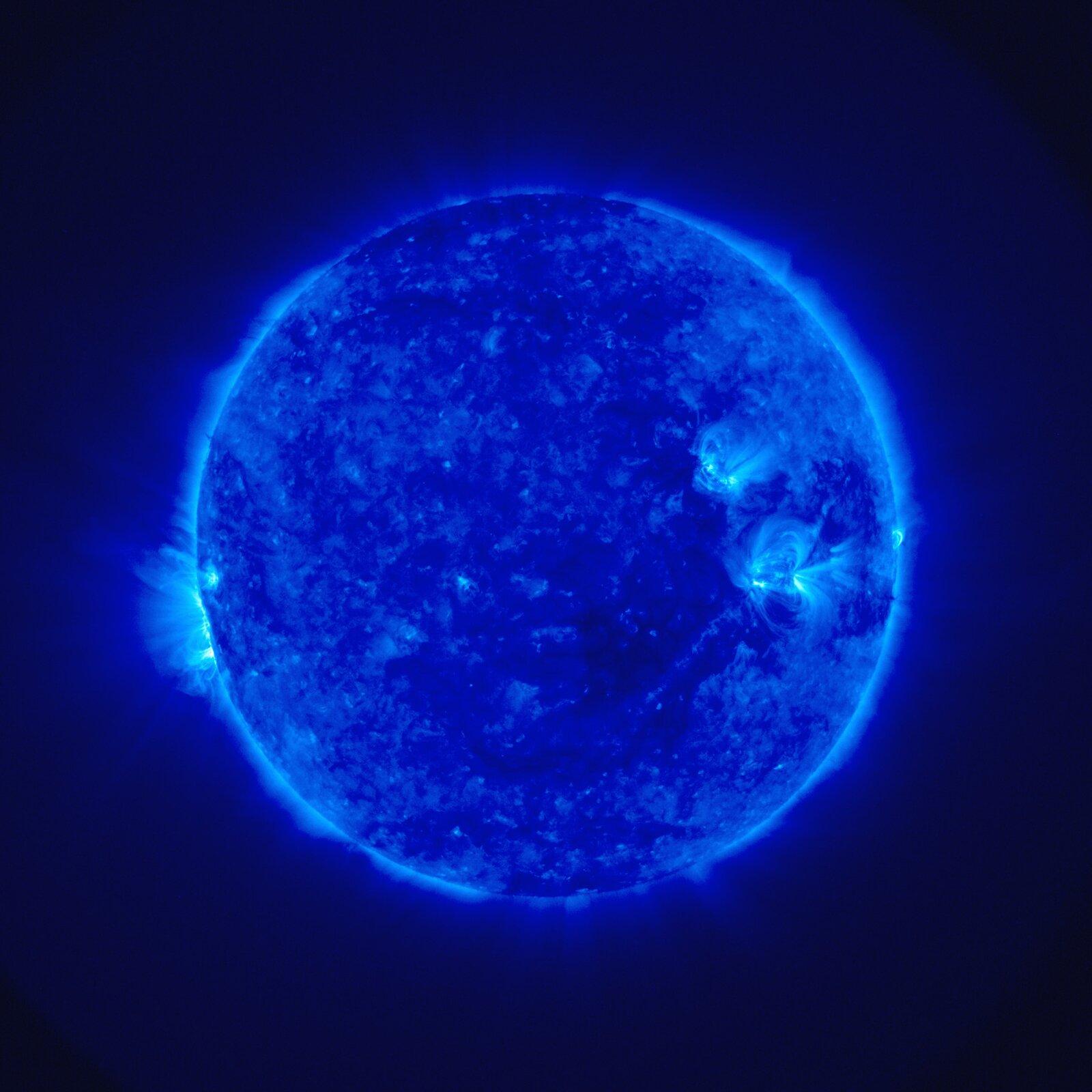 Zdjęcie przedstawia Słońce sfotografowane wultrafiolecie. Tło czarne. Słońce wygląda jak niebieska, luminescencyjna kula.