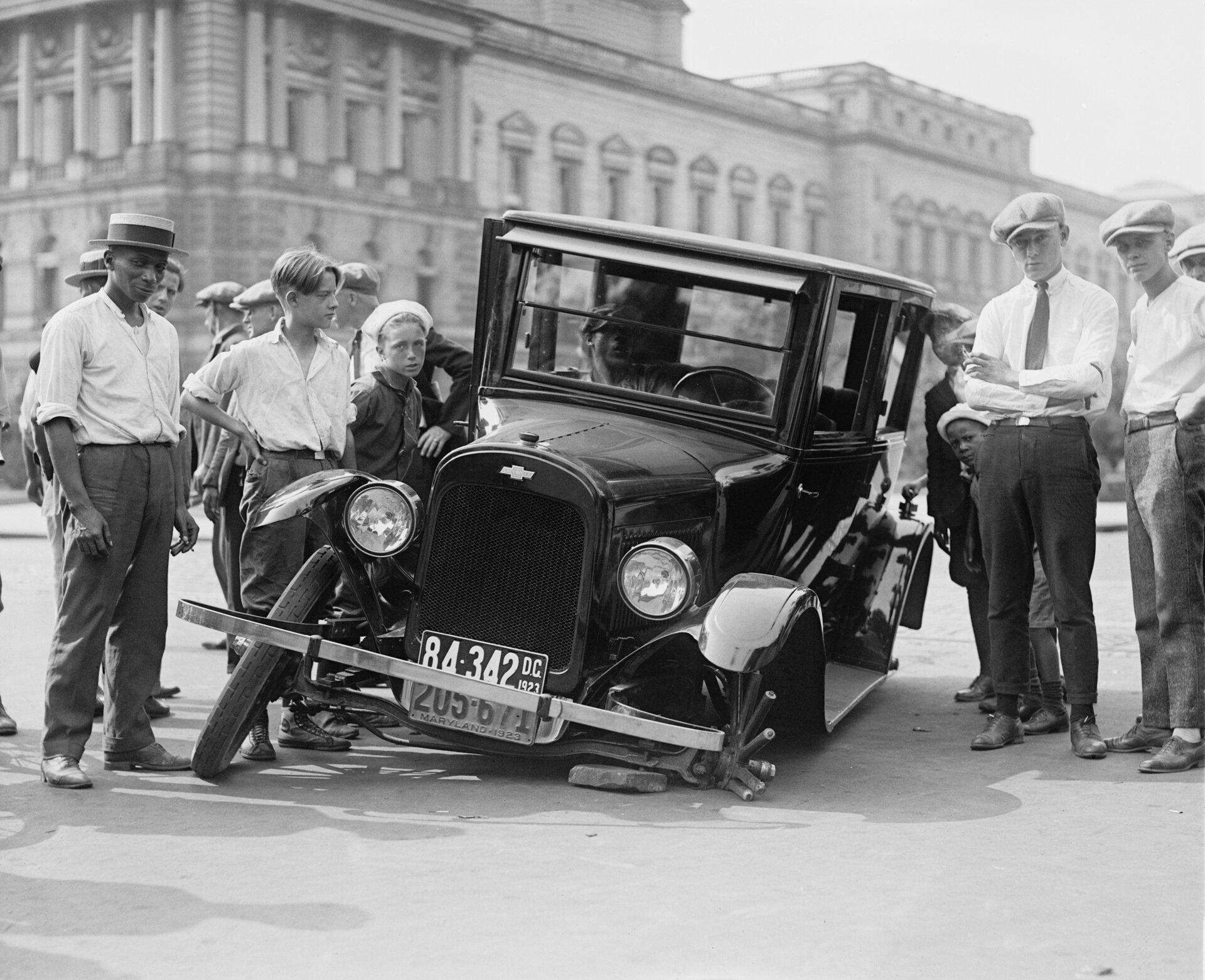 archiwalne zdjęcie, na nim samochód zuszkodzonym kołem; na samochodzie widać podwójne tablice rejestracyjne - dla Dystryktu Columbii istanu Maryland