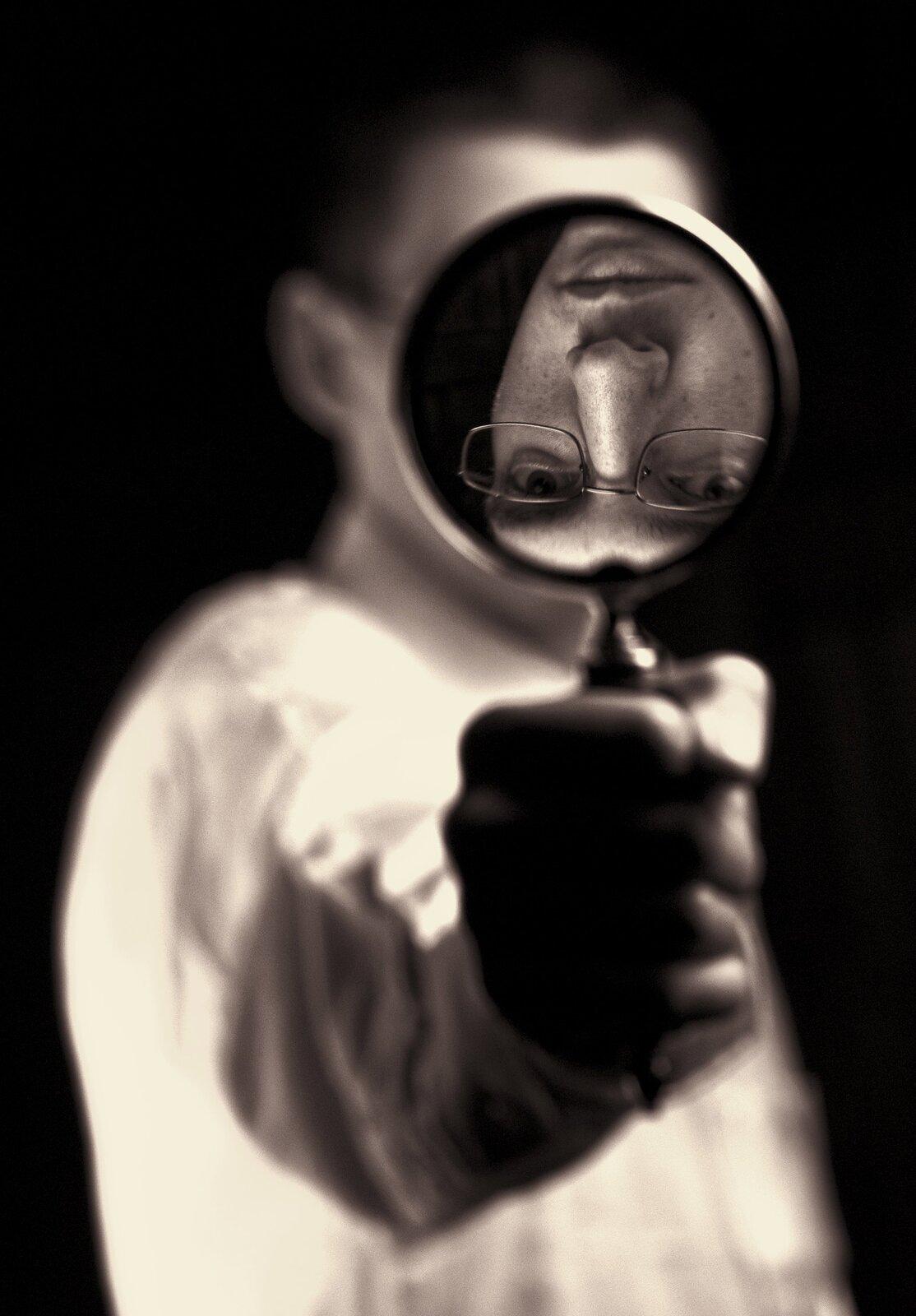 Wykonane wodcieniach sepii zdjęcie przedstawia mężczyznę spoglądającego wstronę aparatu itrzymającego wręce lupę. Człowiek znajduje się poza obszarem ostrości zdjęcia. Ostrość skupiona jest na odwróconym do góry nogami obrazie twarzy tworzącym się wsoczewce lupy. Widać wnim, że mężczyzna nosi okulary ima spokojny wyraz twarzy.