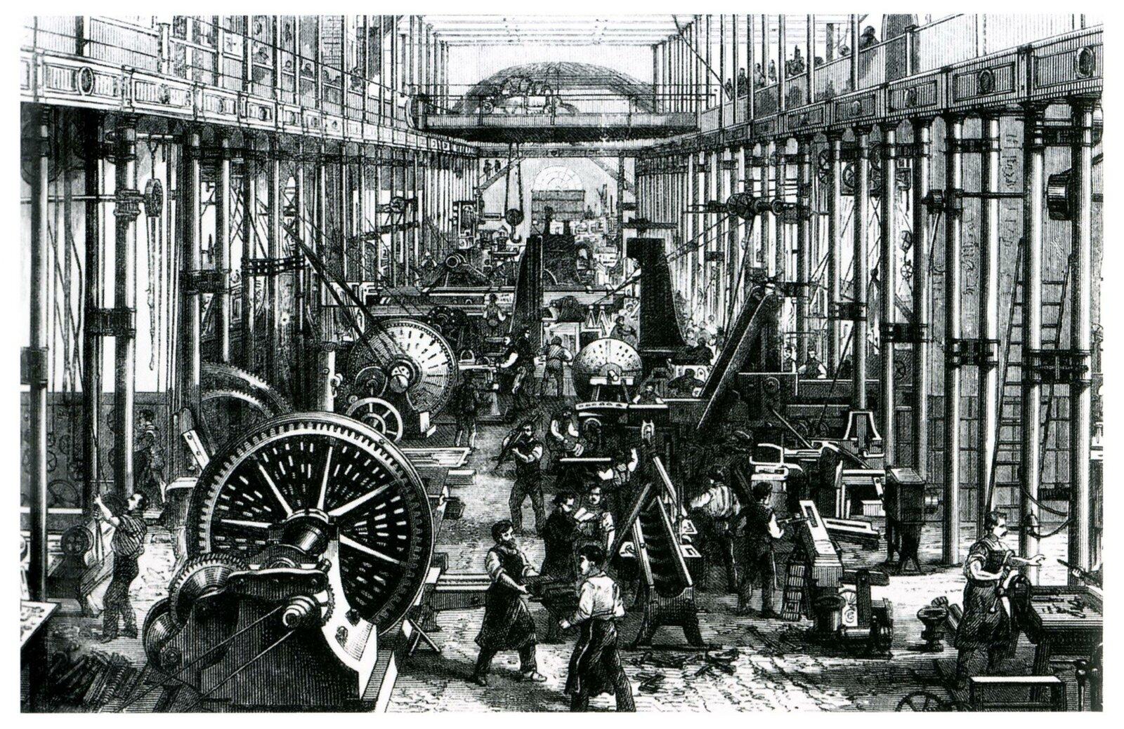 Hala fabryczna wypełniona różnymi maszynami, pomiędzy nimi widać pracujących robotników.