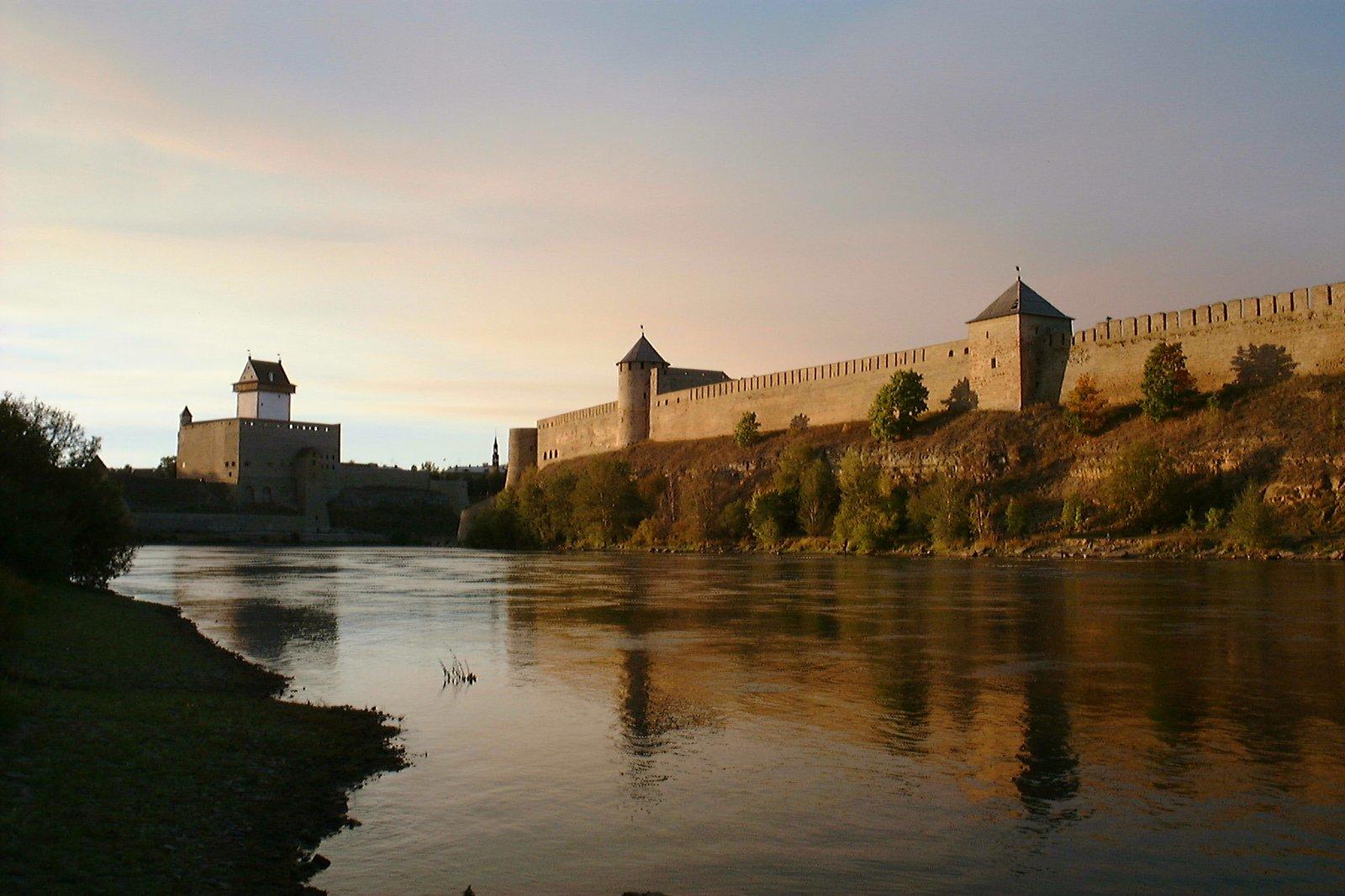 Zdjęcie robione zprzeciwnego brzegu rzeki. Na pionowym brzegu rzeki stoi kamienny, szary mur obronny, wktórym są dwie baszty. Jedna prostokątna, jedna okrągła. Wbasztach są wąskie okna. Dalej, po przeciwnejj stronie rzeki, nad jej brzegiem stoi biała, kwadratowa wieża otoczona murem obronnym