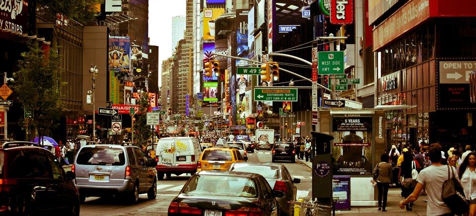 Na zdjęciu zatłoczona ulica wnowoczesnym mieście. Liczne neony, szyldy ireklamy. Wysokie budynki.