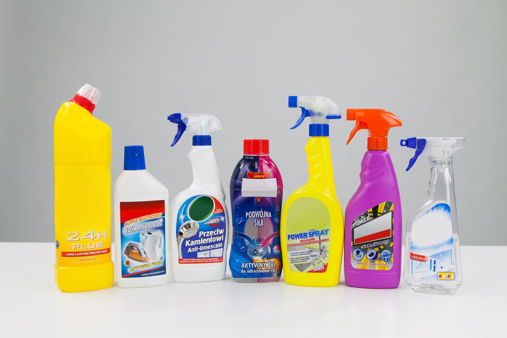 Zdjęcie przedstawia popularne środki czystości wróżnych pojemnikach. Detergenty wpostaci płynu są wpięciu plastikowych butelkach ułożonych wpółokrąg. Po lewej stronie dwie butelki zakończone są ręcznymi spryskiwaczami. Trzecia butelka zakończona pionowo ustawionym dozownikiem, pozostałe dwie mają kolejno korek izakrętkę zzabezpieczeniem przed otwarciem przez dzieci. Przed butelkami, na pierwszym planie pionowo stojące pudełko. Na prawo od pudełka plastikowy mniejszy okrągły pojemnik zzakrętką.