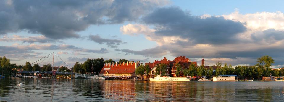 Fotografia prezentuje panoramę wybrzeża portowego wMikołajkach na Mazurach. Na wybrzeżu widoczne zabudowania zczerwonymi dachami oraz cumujące przy brzegu statki iżaglówki.