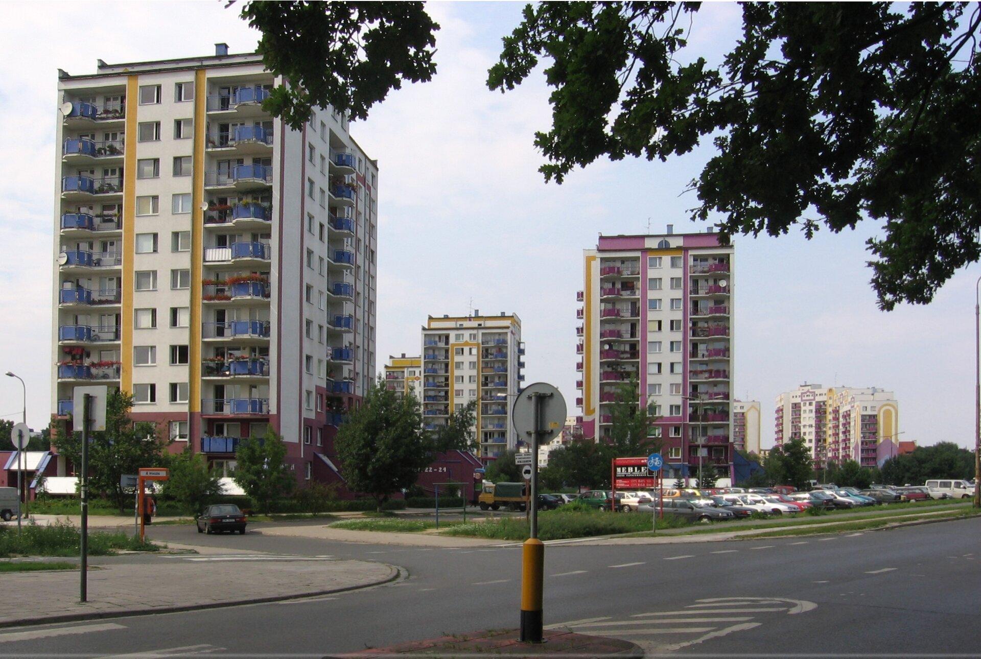 Na zdjęciu wysokie bloki mieszkalne położone przy asfaltowej ulicy. Przed blokami parkingi.