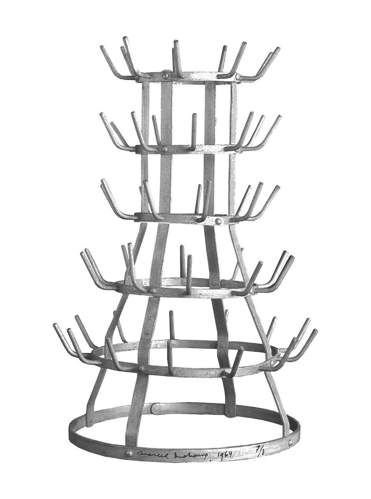 """Ilustracja przedstawia konstrukcję """"Suszarkę do butelek"""" autorstwa Marcela Duchampa. Jest to metalowa konstrukcja składająca się zsześciu okręgów oróżnej wielkości połączonych ze sobą. Okręgi układają się poziomo. Na spodzie jest największy okrąg, akolejne są coraz mniejsze. Koła połączone są czterema wygiętymi, metalowymi listwami stojącymi wpionie. Zokręgów, za wyjątkiem pierwszego wystają metalowe pręty, które przypominają wieszaczki. Są umiejscowione wodstępach dookoła okręgu."""