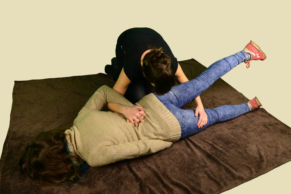 Osoba poszkodowana leży na brzuchu. Noga osoby leżącej, bliższa do kobiety pomagającej wułożeniu poszkodowanej, jest uniesiona. Ręka kobiety ułożona poniżej uniesionej nogi. Dłoń przytrzymuje udo drugiej nogi leżącej na podłożu. Druga ręka kobiety na plecach osoby leżącej. Palce drugiej ręki splecione zpalcami dłoni bliżej kobiety układającej leżącą osobę wpozycji bezpiecznej. Palce dłoni splecione, ręka poszkodowanej osoby zgięta włokciu iułożona na plecach. Druga ręka osoby leżącej umieszczona nadal na podłożu. Dłoń wsunięta pod biodro.