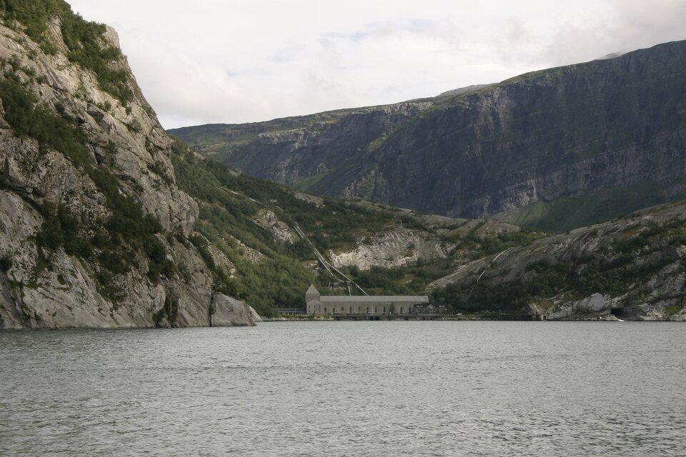 Na zdjęciu zbiornik wodny otoczony przez skaliste stoki. Wtle góry. Wdole elektrownia wodna, murowany szeroki budynek.
