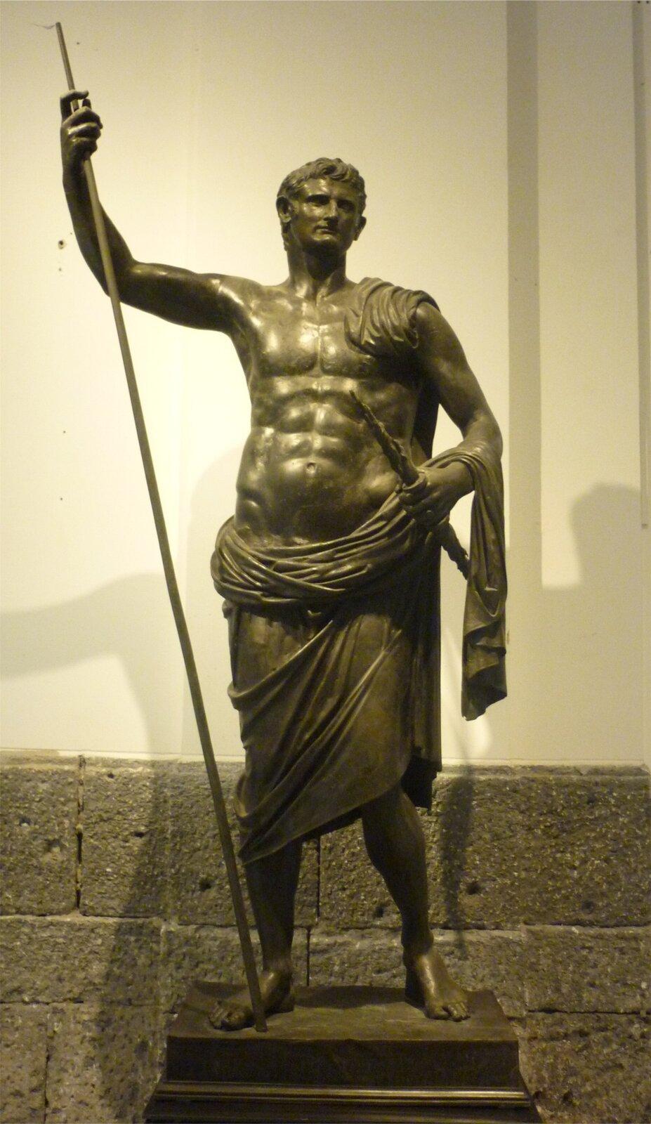 Ilustracja przedstawia posąg Oktawiana Augusta. Rzeźba wykonana jest zbrązu. Ukazuje cesarza, jako młodego umięśnionego mężczyznę. Jest półnagi; szata osłania go od pasa wdół. Ma małą głowę lekko przechyloną wbok. Posąg wyrzeźbiony został zgodnie ze starożytną zasadą ponderacji: ciężar spoczywa na jednej stopie, sylwetka jest lekko esowata. Cesarz wjednej ręce trzyma wysoki drzewiec, wdrugiej krótką rzeźbioną laskę.