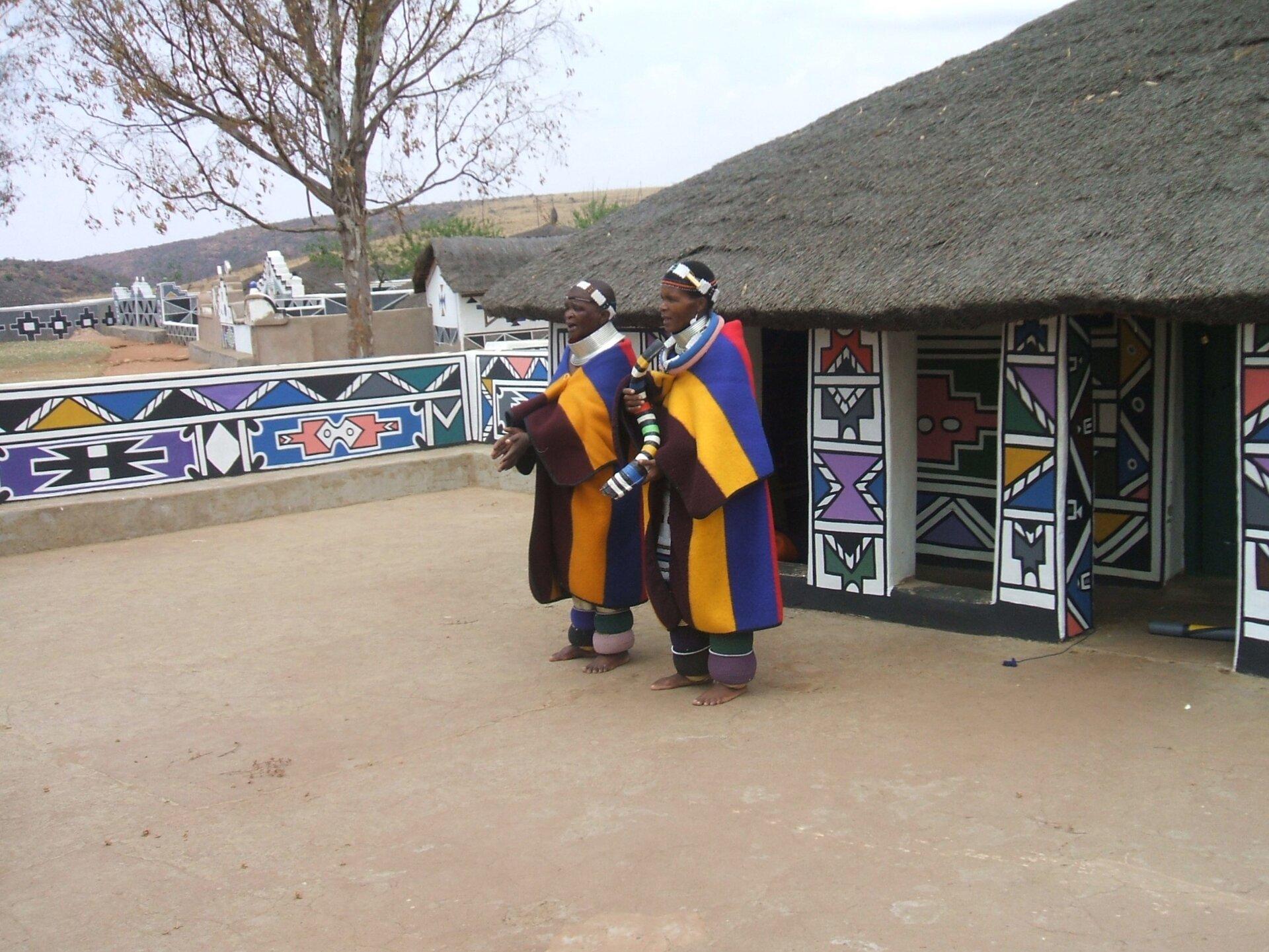Na zdjęciu ciemnoskórzy mieszkańcy Republiki Południowej Afryki wludowych strojach. Wtle chata kryta strzechą, ściany pomalowane wjaskrawe, kolorowe, geometryczne wzory. Dalej teren górzysty.