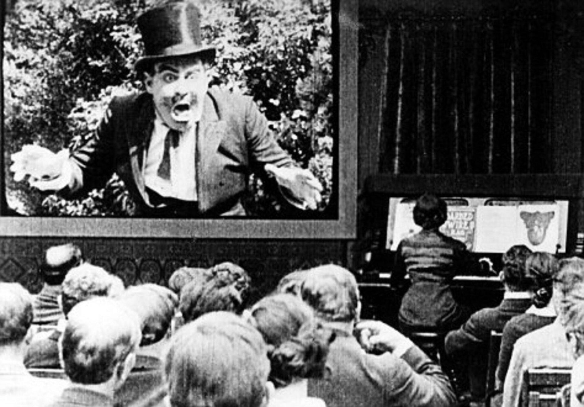 Fotografia przedstawia czarno białe zdjęcie pianisty wniemym kinie. Ilustracja przedstawia tapera wniemym kinie osoba grająca na pianinie lub organach teatralnych, improwizująca podkład muzyczny do wyświetlanych scen.