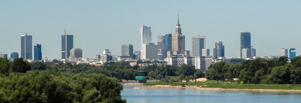 Na zdjęciu wysoka nowoczesna zabudowa biurowa ibloki mieszkalne. Na pierwszym planie rzeka ijej brzegi porośnięte drzewami.