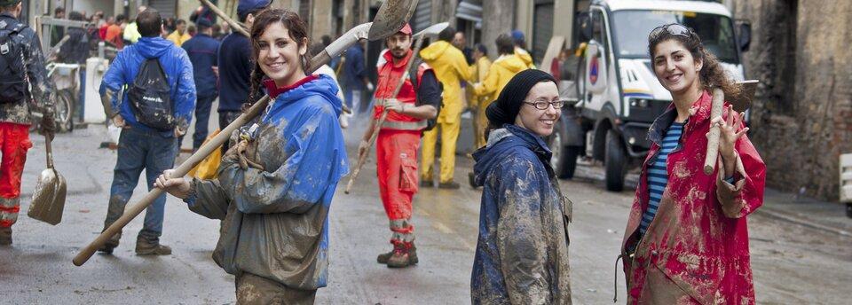 Kolorowe zdjęcie przedstawia ulicę pełną ludzi wubrudzonych błotem ubraniach. Niektórzy znich trzymają wrękach łopaty. Na pierwszym planie znajdują się trzy młode kobiety, zwrócone przodem do obserwatora, uśmiechnięte. Pierwsza zlewej iśrodkowa ubrane są wubłocone niebieskie kurtki, trzecia, stojąca po prawej stronie, ubrana wczerwoną, również ubłoconą na dole kurtkę isweter wniebiesko-czarne pasy. Kobieta pierwsza zlewej ipierwsza zprawej trzymają zarzucone na ramię łopaty. Wtle ludzie wczerwonych, żółtych iniebieskich ubraniach ochronnych. Ulica jest ubłocona, przypomina to sytuację po powodzi.
