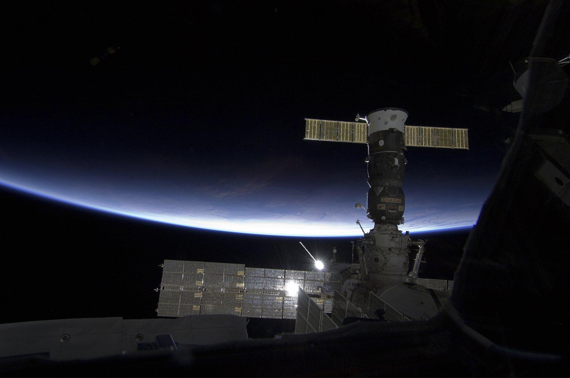 Zdjęcie przedstawia obraz zMiędzynarodowej Stacji Kosmicznej. Na pierwszym planie panele energetyczne iinne elementy konstrukcyjne, daleko wtle ugóry, atak naprawdę daleko poniżej krzywizna Ziemi. Centralna część kadru, wtym fragment linii horyzontu, atakże części stacji znacznie jaśniejsze, oświetlone przez Słońce, które wmomencie wykonywania zdjęcia zasłonięte było największym zpaneli słonecznych.