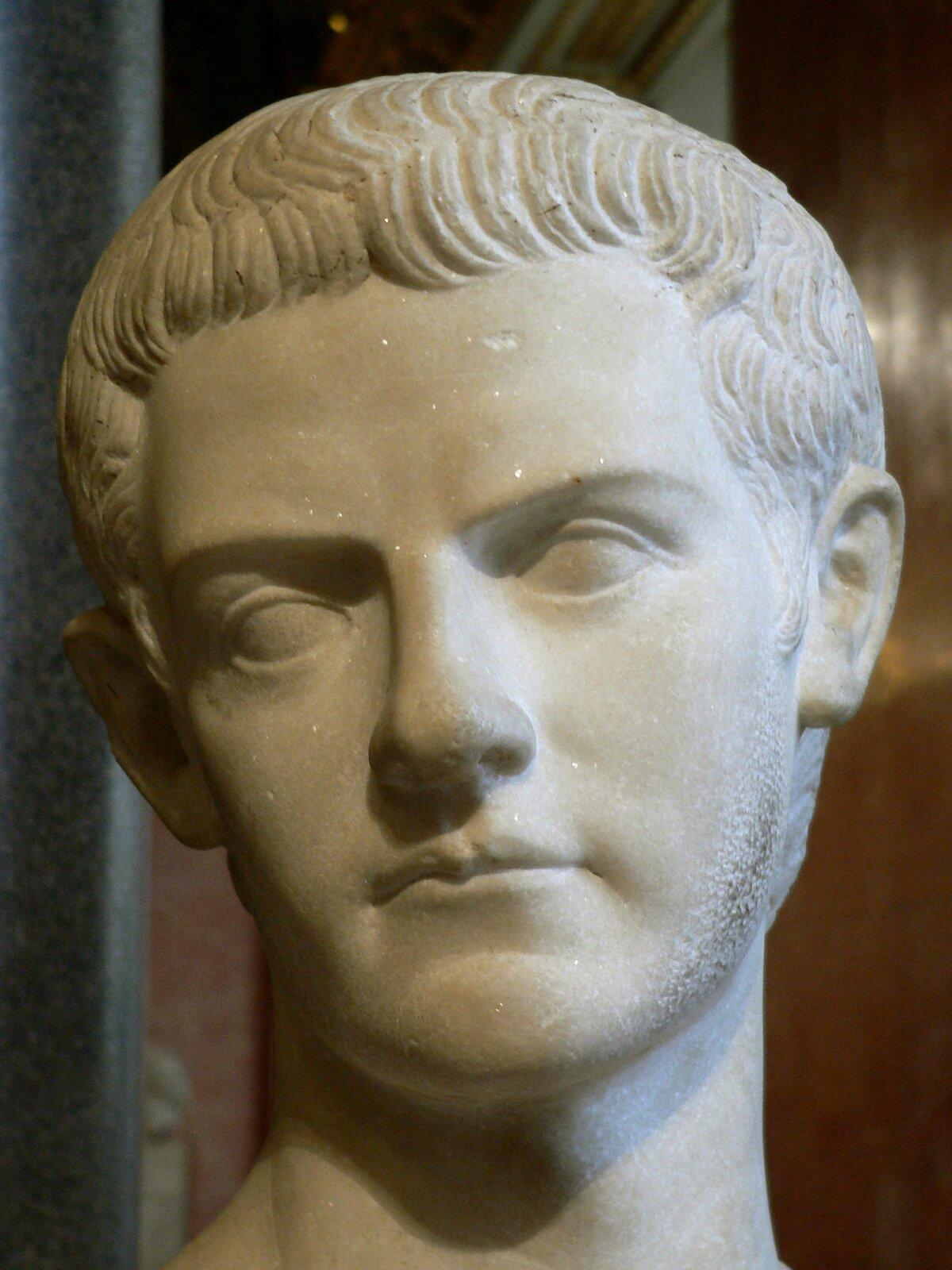 Ilustracja przedstawia marmurowe popiersie cesarza Kaliguli. Władca ukazany jest jako młodzieniec. Ma lekko przechyloną głowę, krótkie włosy iduże oczy.