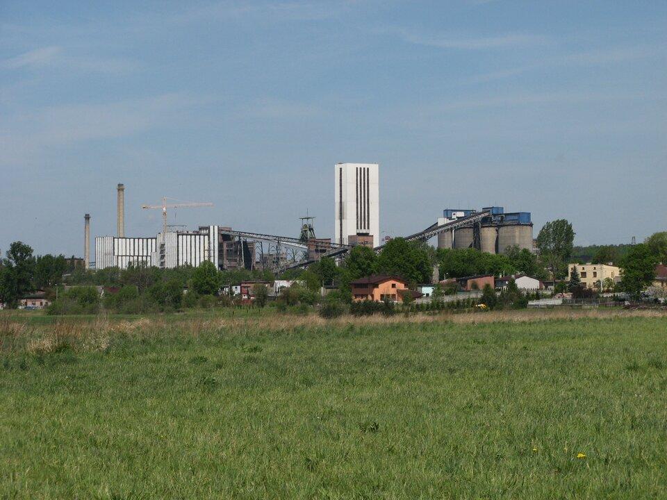 Zdjęcie przedstawia budynki kopalni węgla kamiennego Halemba wRudzie Śląskiej. Słoneczny dzień, lato. Na pierwszym planie duża zielona polana. Na linii horyzontu, wplanie średnim niskie budynki mieszkalne, aza nimi drzewa. Za drzewami budynki kopalni. Wcentrum zdjęcia, najwyższa budowla kopalni, biały budynek wkształcie pionowego prostopadłościanu. Jest to wieża wyciągowa. Na lewo dwa duże budynki, zakład przeróbczy. Ściany budynków pokryte pionowymi prostokątnymi białymi panelami. Za budynkami dwa wysokie okrągłe kominy wykonane zczerwonej cegły. Między kominami awieżą wyciągową, znajduje się szyb górniczy wykonany zbelek stalowych. Na szczycie szybu dwa koła wyciągowe. Po prawej stronie cztery wysokie budowle wkształcie walców ośrednicy około dziesięciu metrów wszarym kolorze. To zbiorniki na węgiel. Wysokość budynków to połowa wysokości wieży wyciągowej. Dwa taśmociągi sięgają aż do dachu zbiorników na węgiel.