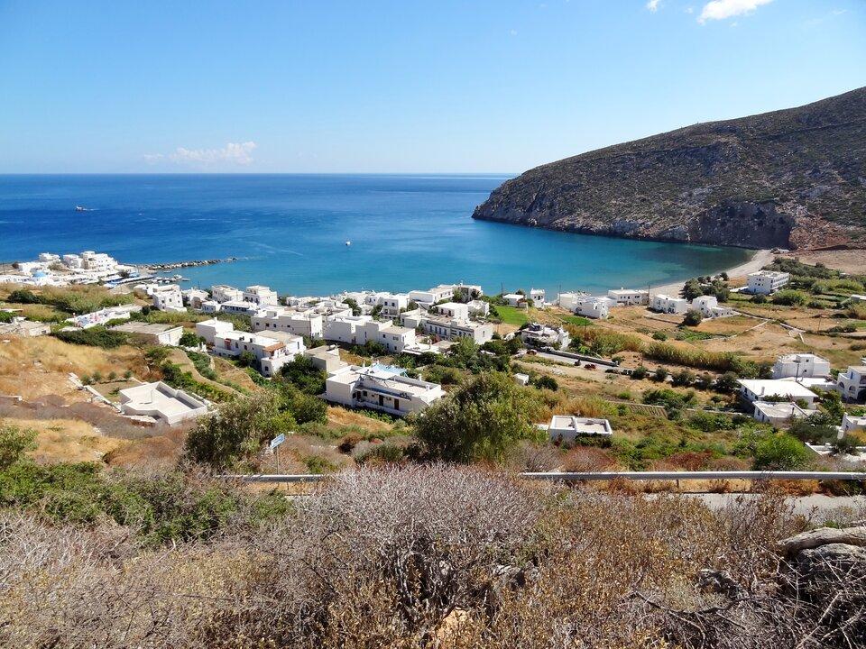 Na zdjęciu zatoka. Piaszczysta plaża. Białe zabudowania zpłaskimi dachami. Skąpa roślinność. Brzeg górzysty.
