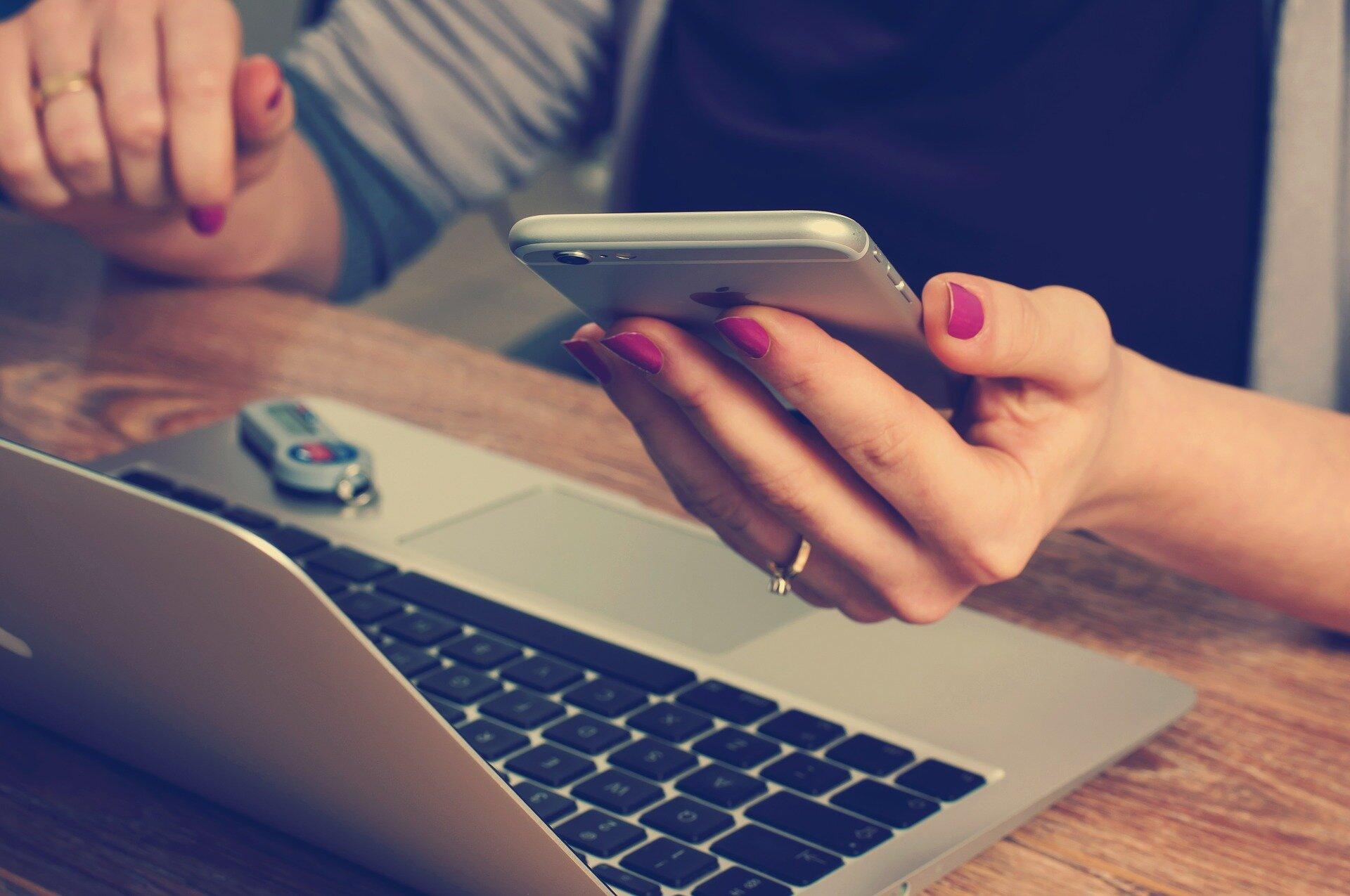 Fotografia kobiecej dłoni, trzymającej telefon