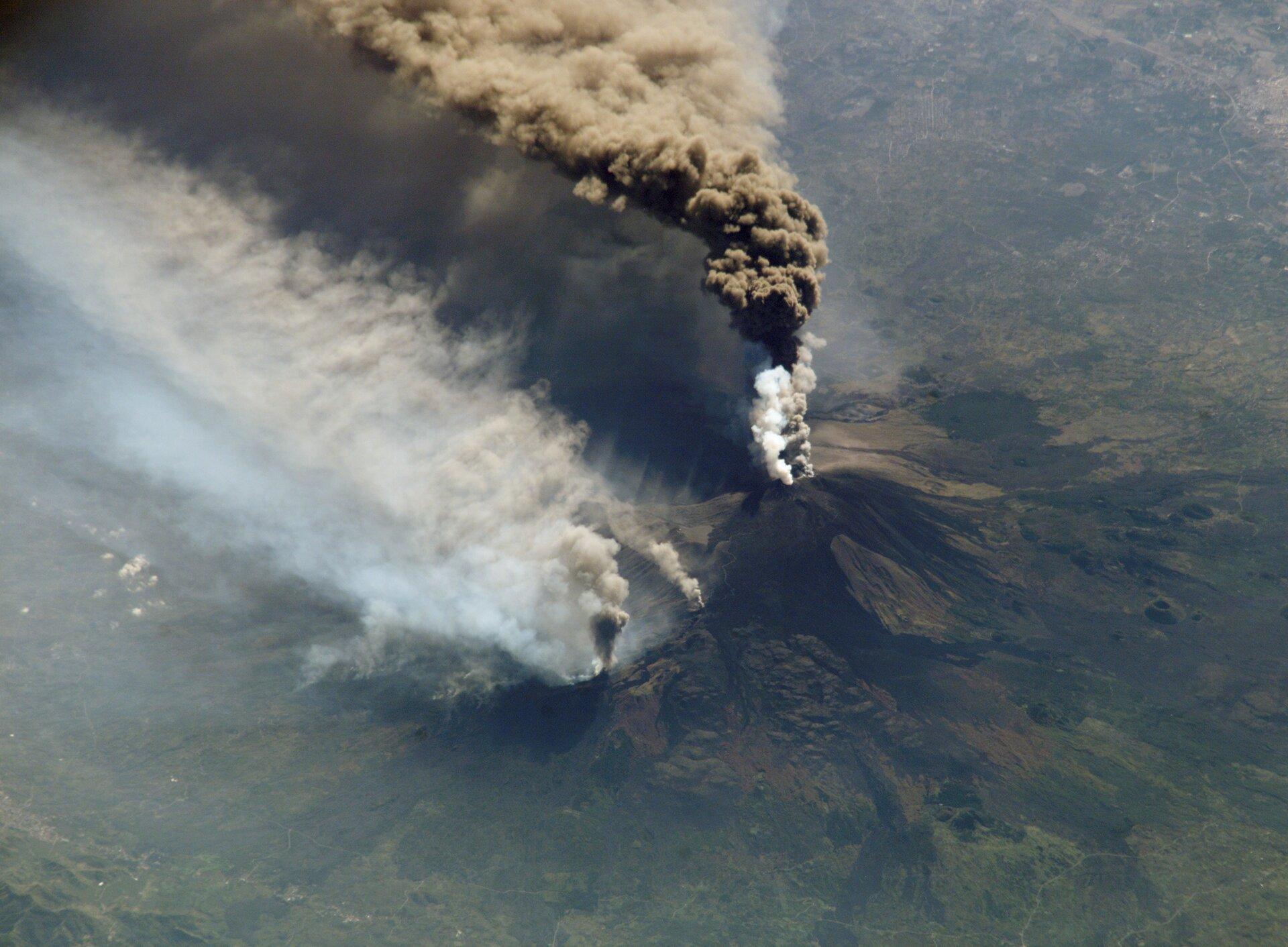 Fotografia wykonana zgóry przedstawia wulkan podczas erupcji. Ze szczytu wulkanu wydobywa się chmura biało-brazowych gazów ipyłów.