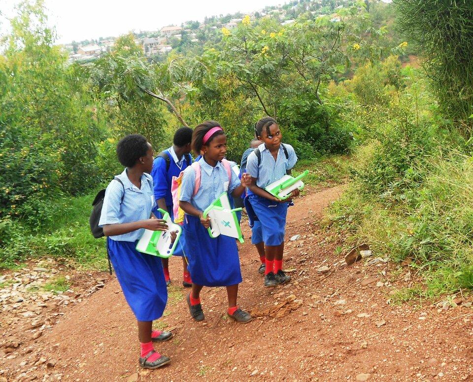 Na zdjęciu ciemnoskórzy uczniowie iuczennice wjednolitych strojach uczniowskich. Błękitne bluzki, niebieskie spódnice – dziewczęta, chłopcy noszą spodnie. Wszyscy mają wrękach zielone laptopy. Dzieci idą drogą wśród zieleni. Droga pokryta czerwoną glebą.