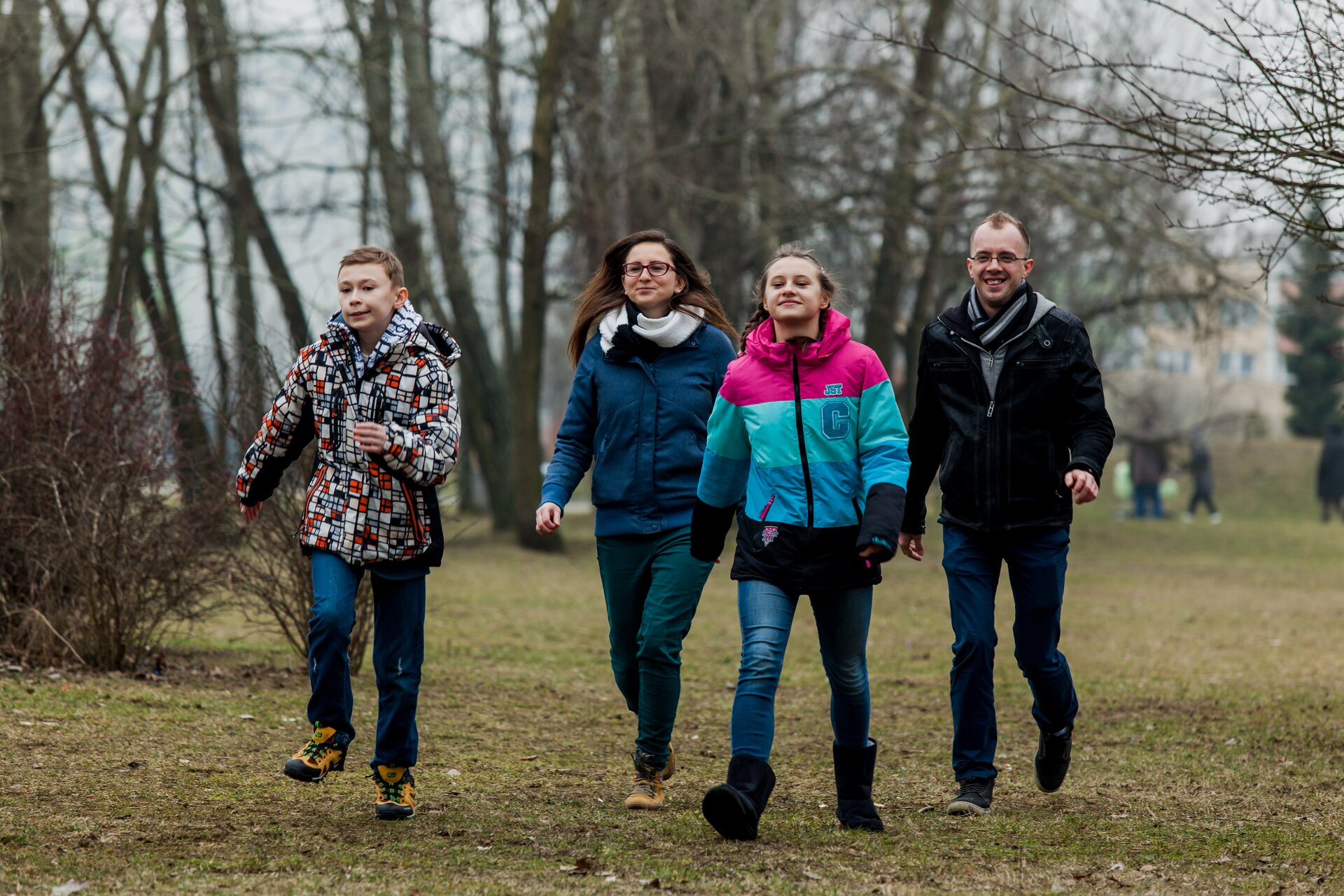 Fotografia przedstawia cztery osoby biegające lub spacerujące szybkim krokiem po jesiennym parku.