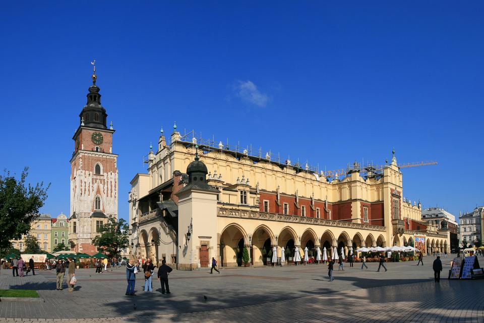 Fotografia prezentuje Rynek Starego Miasta wKrakowie. Na pierwszym planie widoczny budynek Sukiennic, przed którym spacerują ludzie.