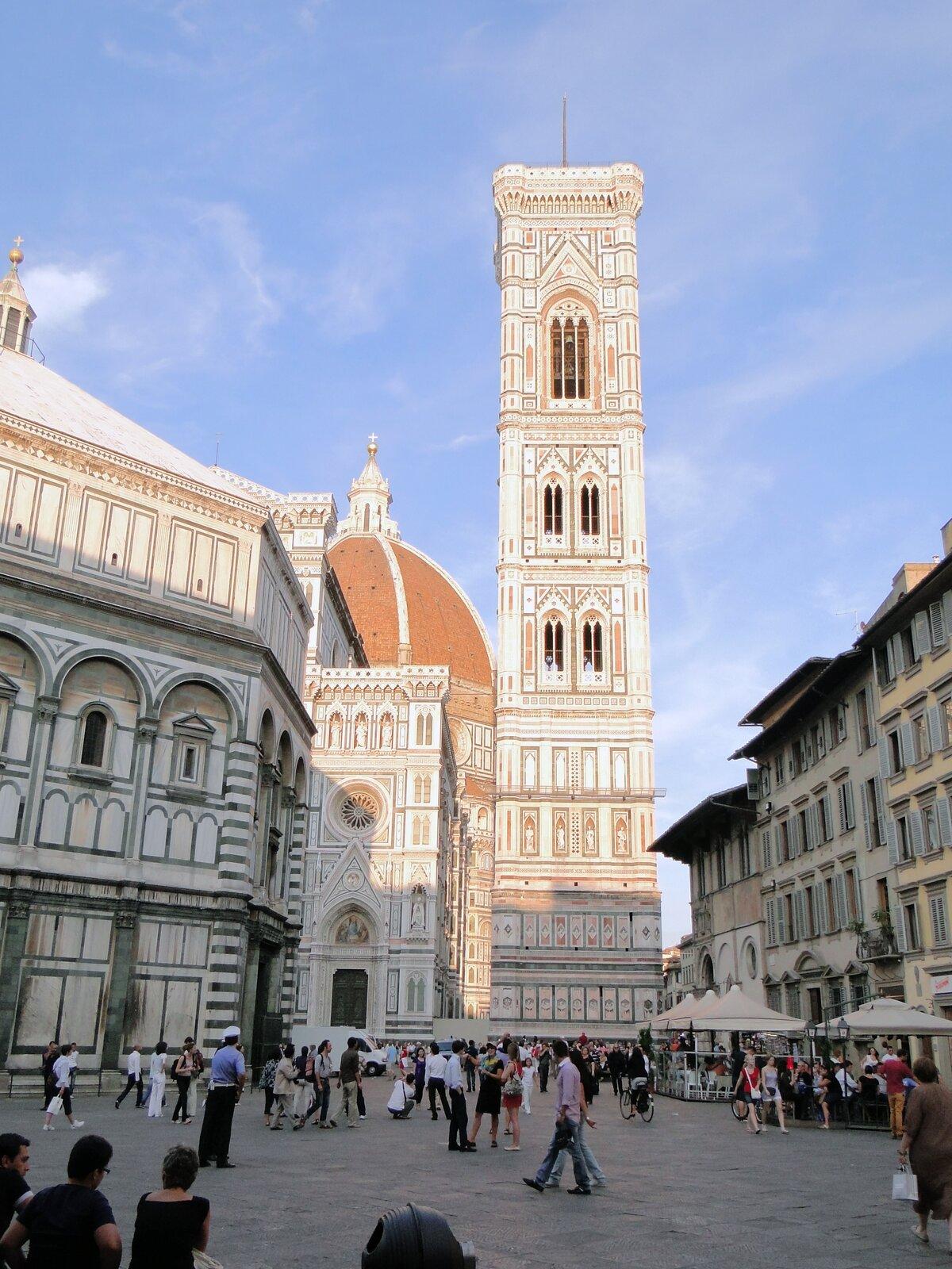 Ilustracja przedstawia dzwonnicę Giotta na placu we Florencji. Jest to wieża okwadratowej podstawie zgraniastymi wzmocnieniami wnarożnikach. Elewacje zostały obłożone kolorowymi płytami marmuru okolorze białym iróżowym. Wieża posiada potrójne okno wnajwyższej kondygnacji oraz dwie pary podwójnych okien wkondygnacjach niższych. Wszystkie okna są zakończone łukami ostrymi. Przed dzwonnicą znajduje się plac, przy którym ustawione są budowle. Za budynkami po lewej widoczny jest fragment kopuły ielewacji kościoła Santa Maria del Fiore. Wtle rozciąga się niebieskie niebo.