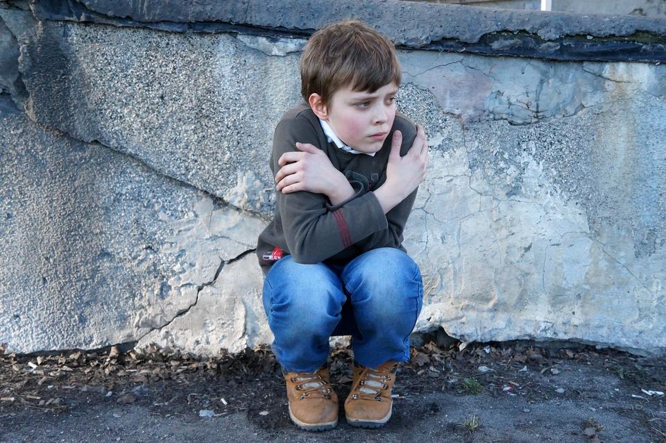 Kolorowe zdjęcie przedstawia dziesięcioletniego chłopca, który przykucnął przy ścianie budynku. Chłopiec jest zwrócony przodem do odbiorcy, twarz skierowana wprawo. Ręce ma skrzyżowane na klatce piersiowej. Dłonie obejmują barki. Chłopiec ubrany wszary wełniany sweter, niebieskie jeansy oraz brązowe sznurowane buty.