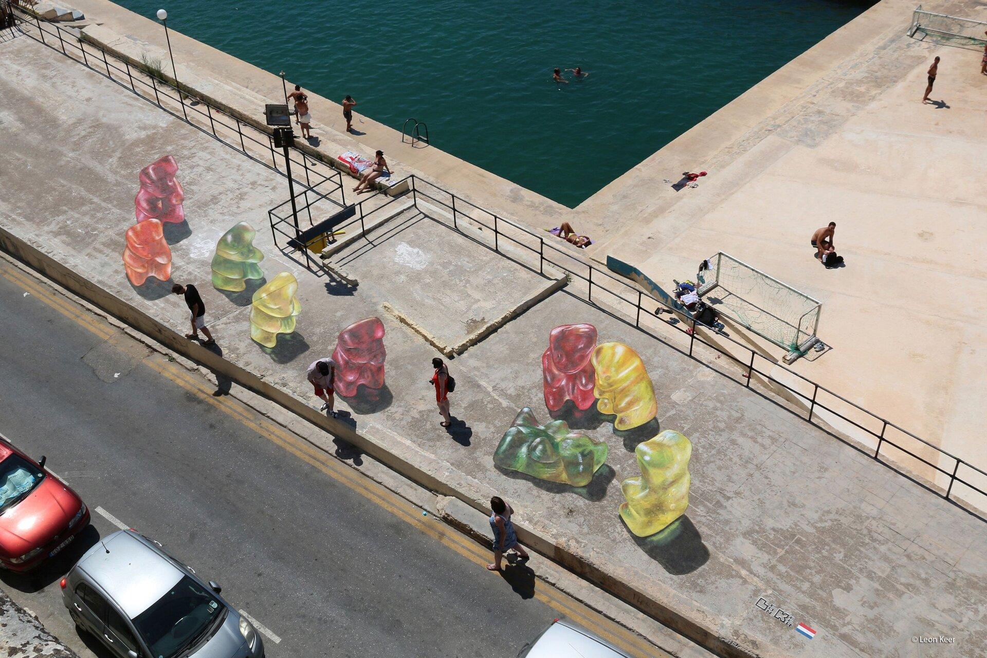 Zdjęcie przedstawia graffiti 3d, ukazujące wielkoformatowe kolorowe misie-żelki.