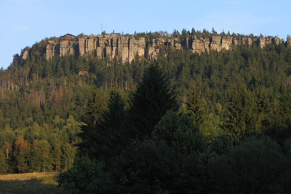 Fotografia prezentuje wysokie opłaskich szczytach skały ,otoczone licznymi drzewami.
