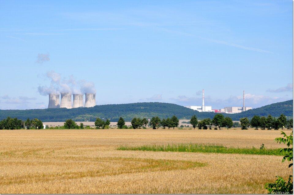 Na zdjęciu na pierwszym planie płaskie tereny rolnicze, na drugim planie za pasmem łagodnych wzniesień cztery grube dymiące kominy izabudowania przemysłowe zwysokimi kominami.