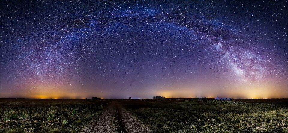 Zdjęcie przedstawiające panoramę nocną zodległymi światłami większego miasta. Na pierwszym planie znajduje się polna droga znieużytkami po bokach. Droga prowadzi prosto wstronę horyzontu. Na niebie ogromna liczba gwiazd zwyraźnie odznaczającą się Drogą Mleczną tworzącą ogromny łuk nad całym kadrem.