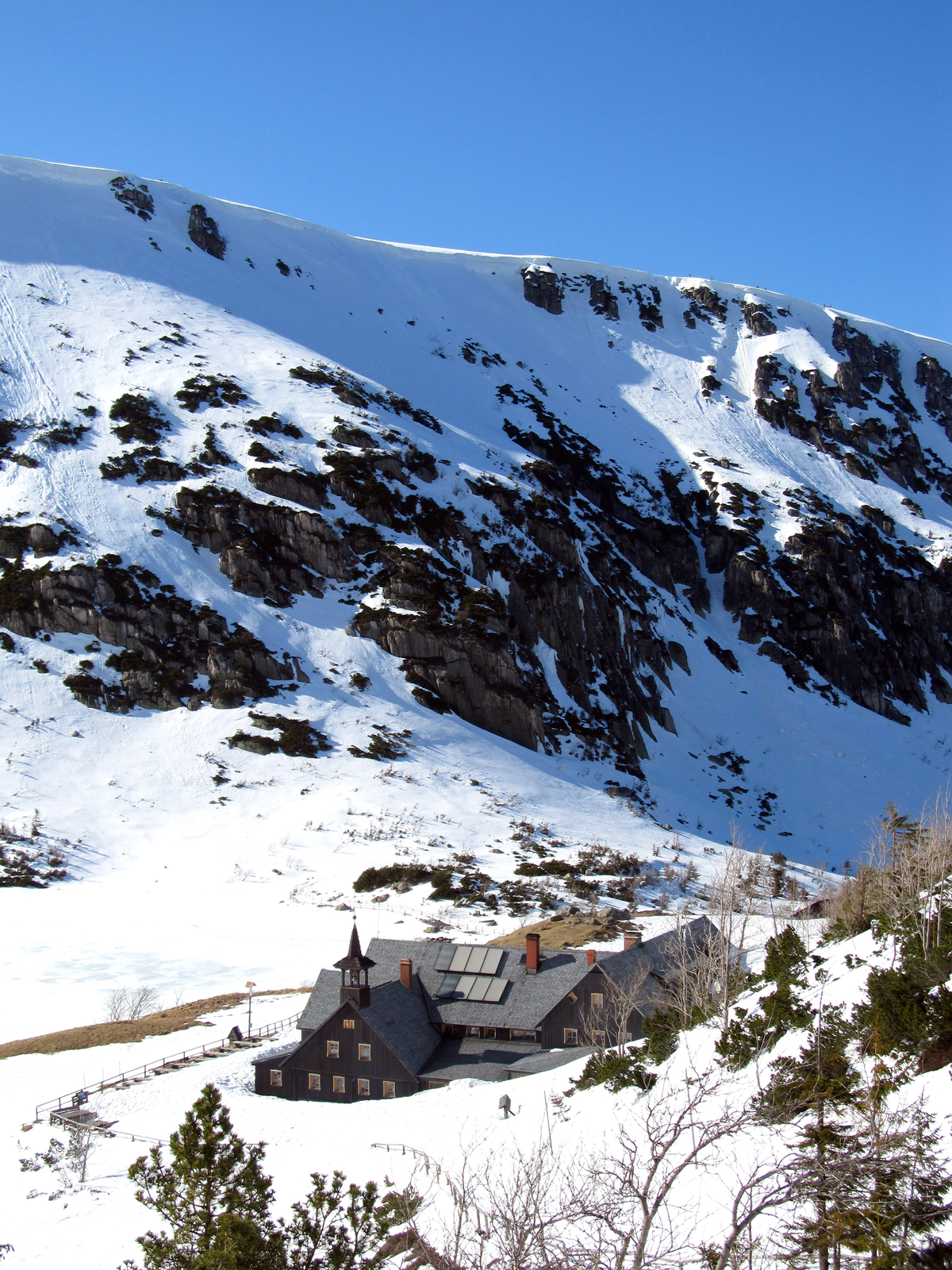 Fotografia prezentuje dolinę górską, otoczoną wysokimi ośnieżonymi szczytami, na dnie której znajduje się schronisko górskie Samotnia.