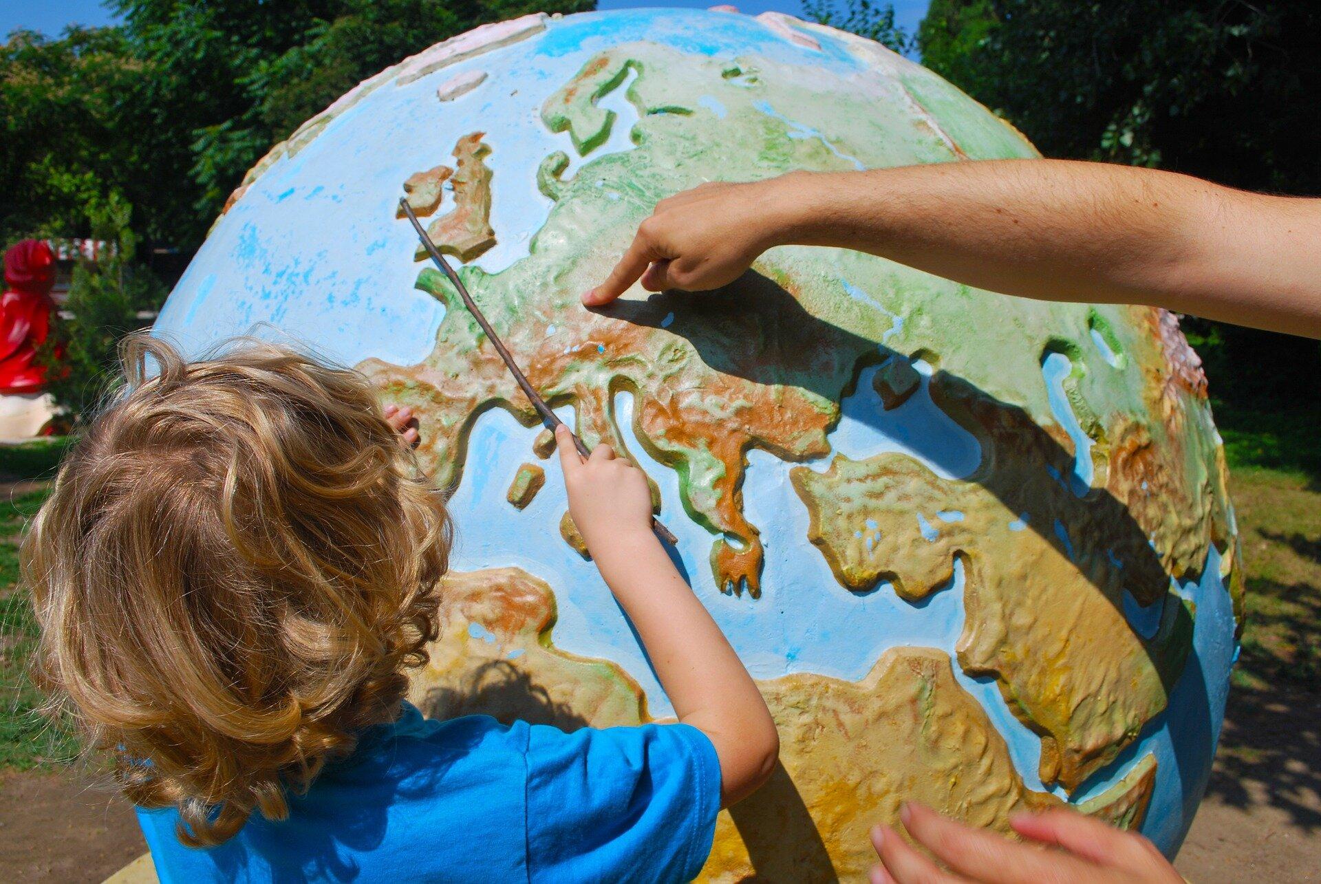 Na zdjęciu dziecko wskazuje patyczkiem na globusie Wyspy Brytyjskie. Druga, niewidoczna na zdjęciu osoba, palcem wskazuje miejsce wcentrum Europy. Globus jest bardzo duży, stoi na dworze, ztyłu drzewa.