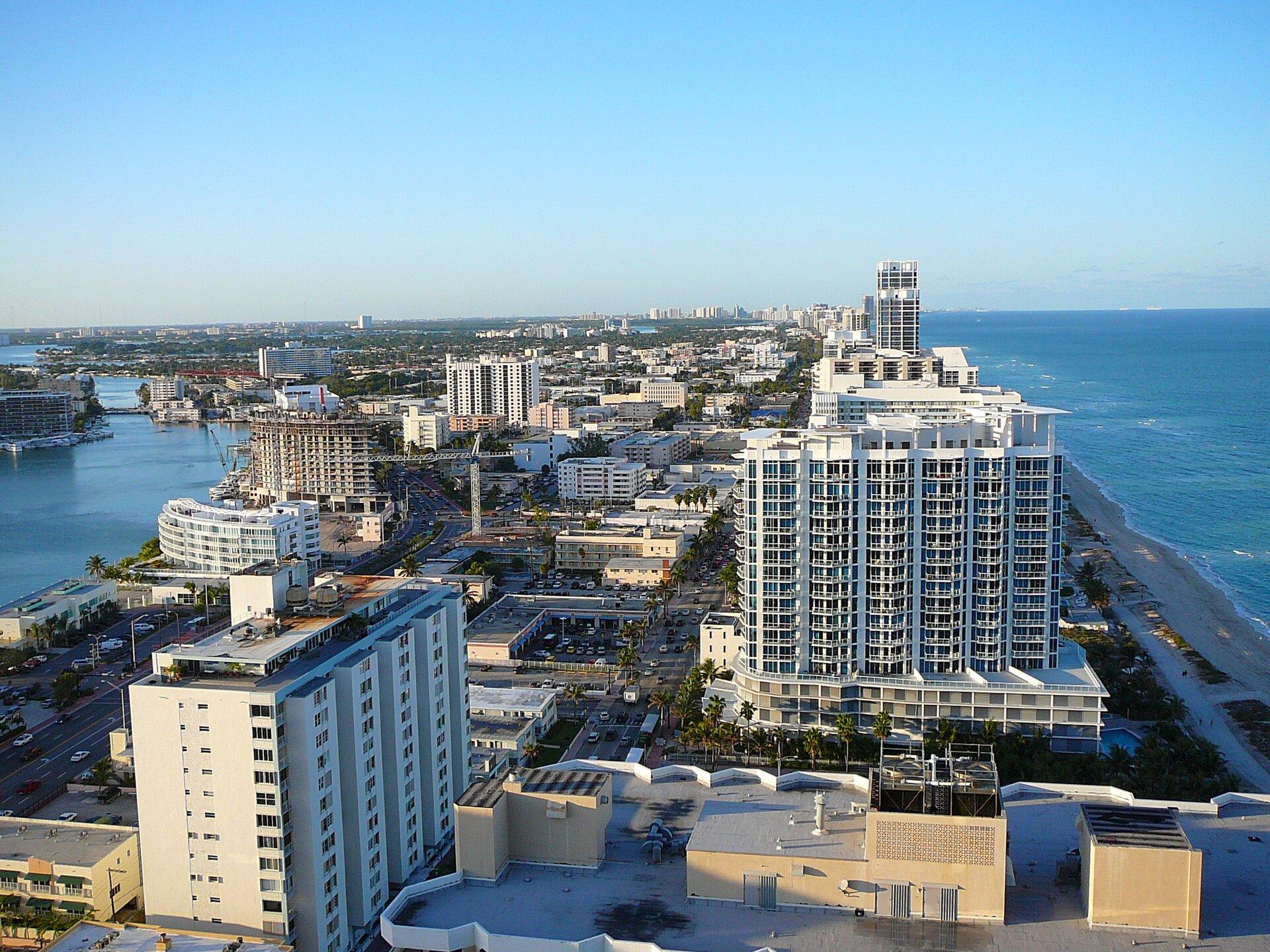 Na zdjęciu nowoczesne miasto wwysoką iniską zabudową położone przy brzegu morza.