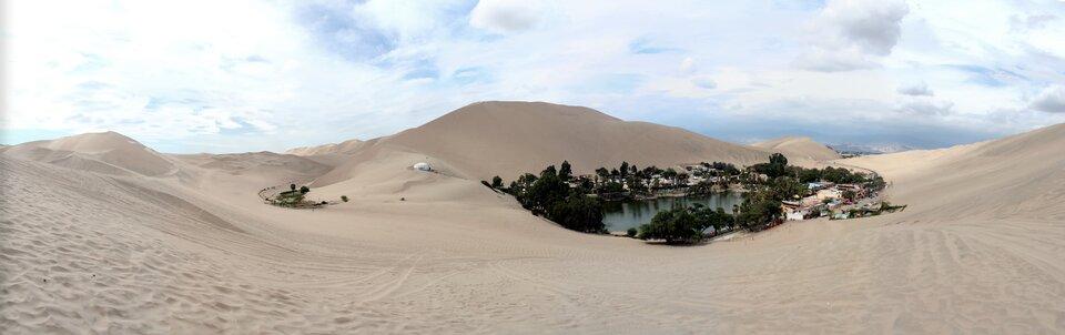 Na zdjęciu pustynia piaszczysta. Teren pofałdowany, widoczne wydmy. Pomiędzy wydmami oaza. Na środku zbiornik wodny, dookoła drzewa. Zabudowania.