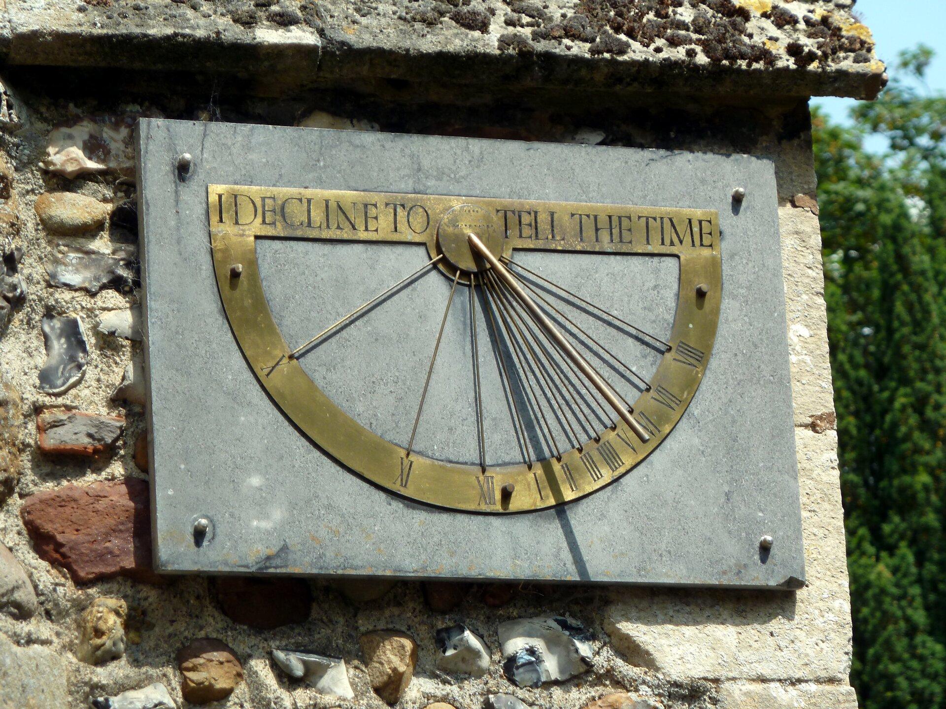 Fotografia prezentuje zegar słoneczny umieszczony na ścianie budynku. Zegar zbudowany jest zprostokątnej płyty, na której umieszczono metalowy półokrąg zrzymskimi cyframi od 1 do 12. Na środku tarczy zegara przymocowano pionową wskazówkę, której cień znajduje się pomiędzy cyfrą 1 a2.