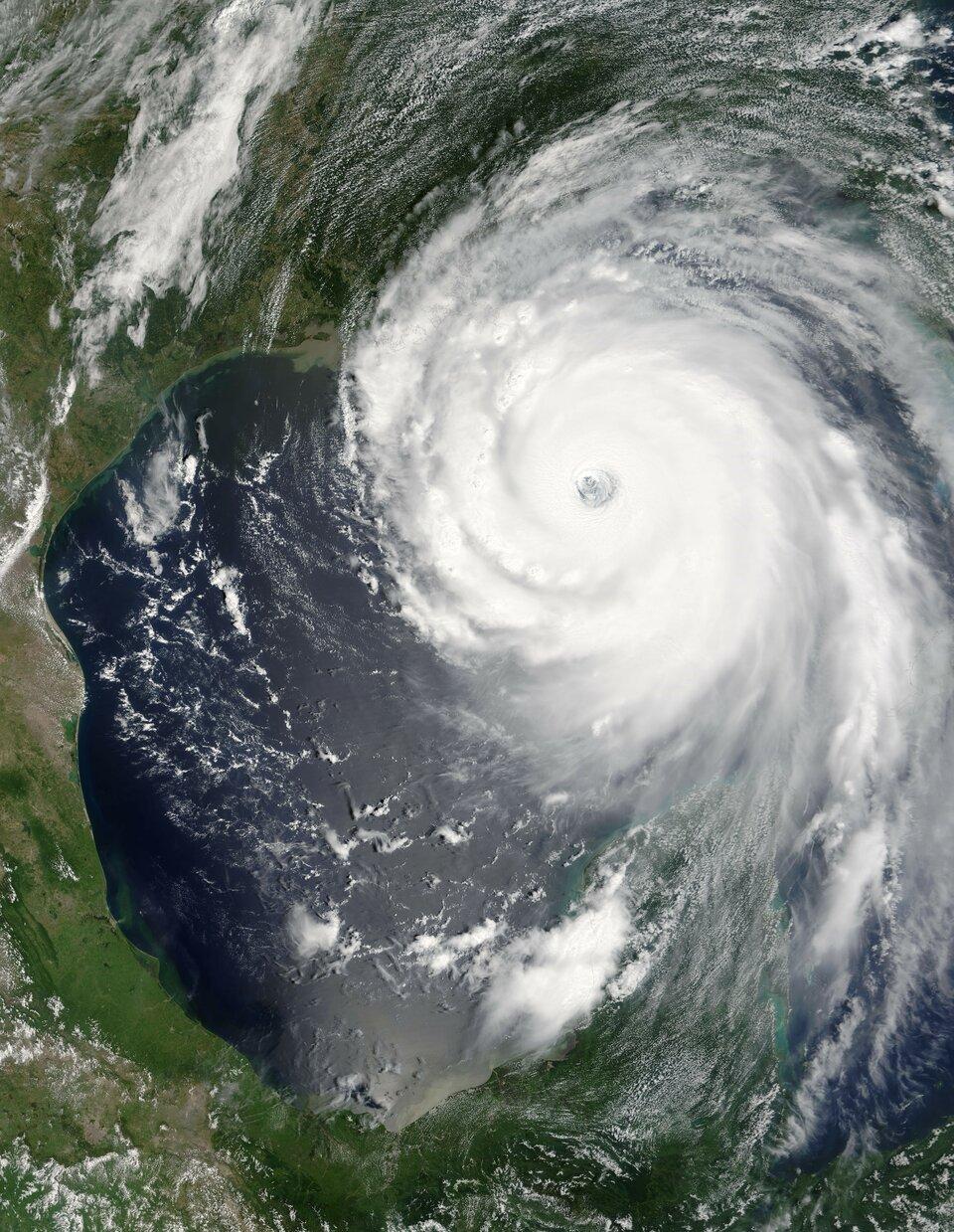 Zdjęcie satelitarne przedstawia huragan oglądany zorbity okołoziemskiej. Na środku zdjęcia białe chmury ułożone wkształt spirali lub wiru. Chmury skręcają się przeciwnie do ruchu wskazówek zegara. Wcentrum spirali znajduje się pusty obszar, czyli oko huraganu. Wobszarach skupiska spiralnie skręconych chmur ipo jego lewej stronie zielony kontynent iciemnoniebieskie wody oceanu.