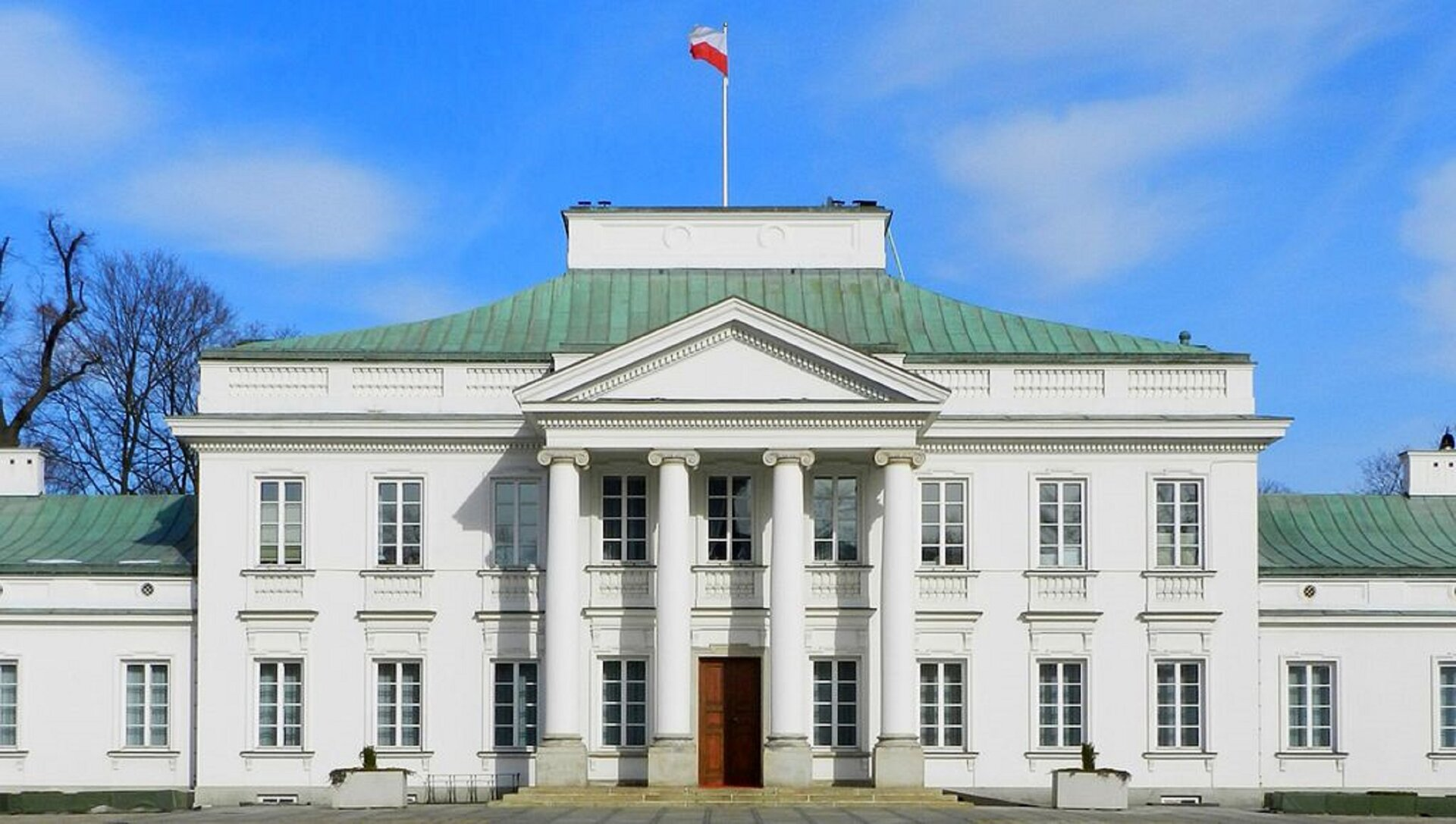 """Ilustracja przedstawia """"Pałac Belwederski"""" wWarszawie. Zdjęcie prezentuje budynek od frontu. Jego fasada jest symetryczna. Pośrodku znajduje się zwieńczony trójkątnym tympanonem portyk, wsparty na czterech jońskich kolumnach. Skrzydła boczne to dwie kondygnacje zsymetrycznie rozmieszczonymi oknami. Pokryty zielona dachówką dach jest czterospadowy, zwieńczony nadbudówką."""