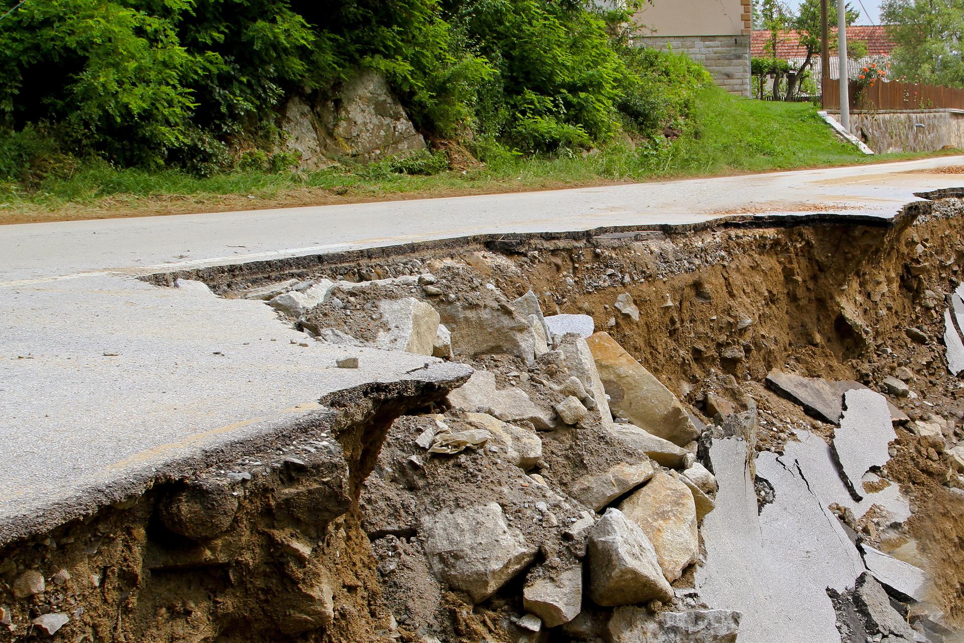 Fotografia prezentuje osuwisko na jezdni. Widoczne oderwane kawałki asfaltu leżące na zapadłym zboczu.