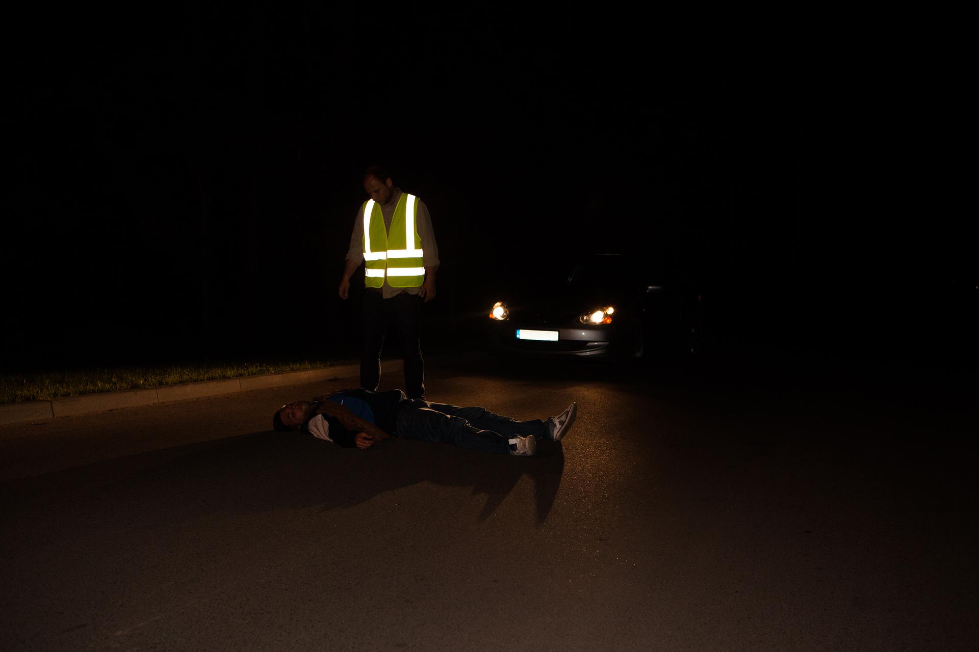Dwa zdjęcia: dwa zdjęcia ułożone poziomo. Noc. Drugie zdjęcie po prawej. Na jezdni leży nieprzytomna osoba. Leżąca osoba ubrana na czarno bez odblaskowych dodatków. Za leżącą osobą zaparkowany samochód zwłączonymi reflektorami. Reflektory skierowane na leżącą osobę. Kierowca wżółtej kamizelce odblaskowej wyróżnia się na ciemnym zdjęciu. Białe pasy na kamizelce ostrzegają innych kierowców.