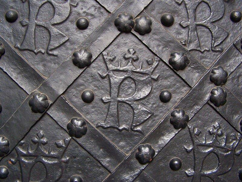 Fotografia przedstawiająca fragment drzwi katedry wawelskiej. Na kutych, żelaznych drzwiach, umieszczone są wszachownicy litery K, anad nimi korony.