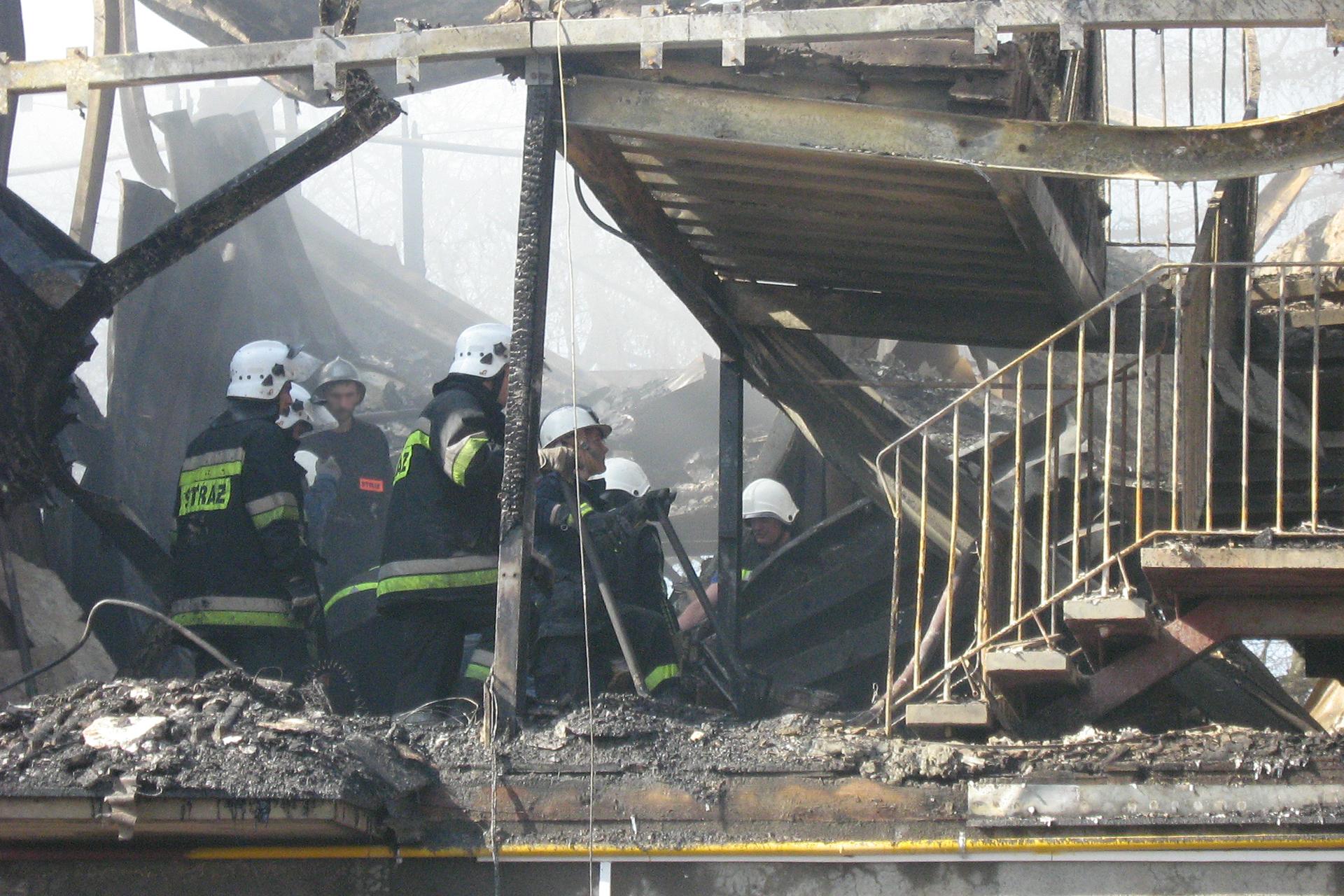 Kolorowe zdjęcie przedstawia akcję ratunkową podczas katastrofy budowlanej. Zdjęcie wykonane wciągu dnia. Na piętrze zawalonego budynku grupa strażaków sprawdza gruz wokół. Po prawej stronie metalowe poręcze wokół schodów. Stropy imetalowe podpory powyginane.