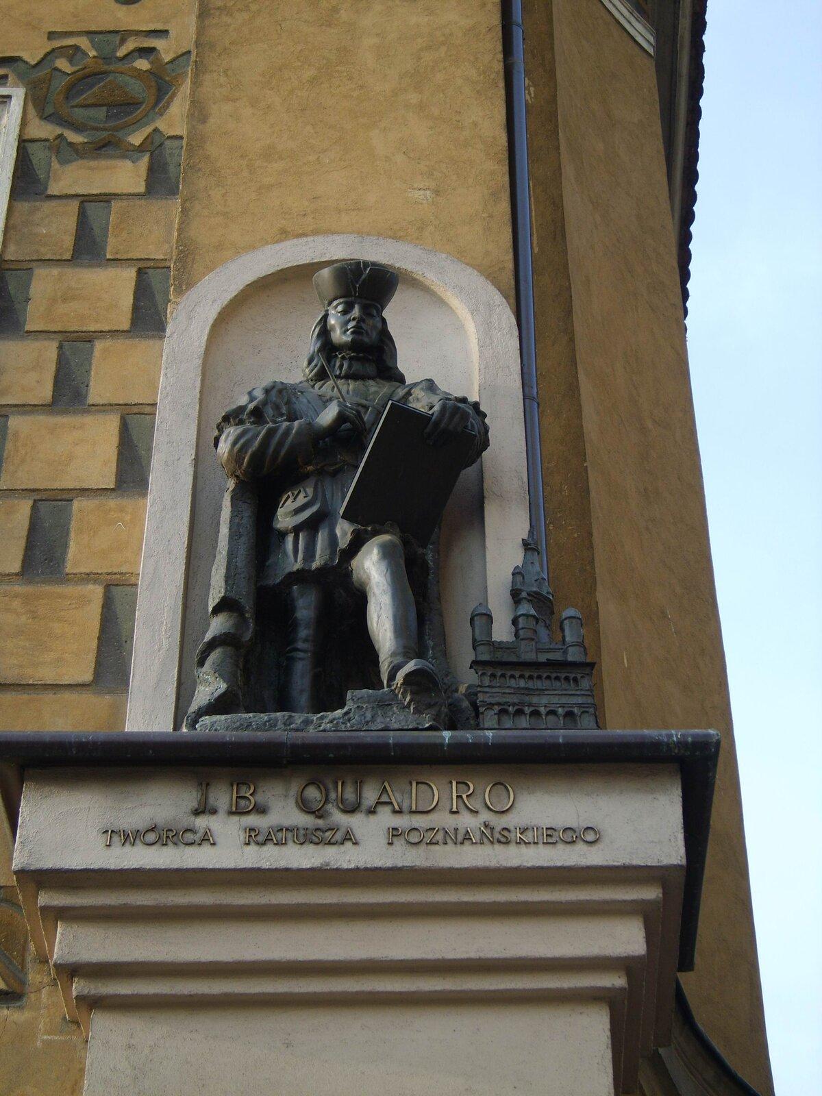 """Rzeźba Jana Baptysty Quadro (Giovanni Battista di Quadro).Rzeźbapowstała wXX w. na kamienicy wPoznaniu, wktórej mieszkał budowniczy. Quadro pochodził zokolic jeziora Como, na pograniczu włosko-szwajcarskim. Ztych okolic pochodziło wielu budowniczych pracujących wEuropie Środkowej – wNiemczech, Czechach, na Śląsku wPolsce. Zwano tych architektów """"komaskami"""" (od nazwy jeziora Como). Rzeźba Jana Baptysty Quadro (Giovanni Battista di Quadro).Rzeźbapowstała wXX w. na kamienicy wPoznaniu, wktórej mieszkał budowniczy. Quadro pochodził zokolic jeziora Como, na pograniczu włosko-szwajcarskim. Ztych okolic pochodziło wielu budowniczych pracujących wEuropie Środkowej – wNiemczech, Czechach, na Śląsku wPolsce. Zwano tych architektów """"komaskami"""" (od nazwy jeziora Como). Źródło: domena publiczna."""